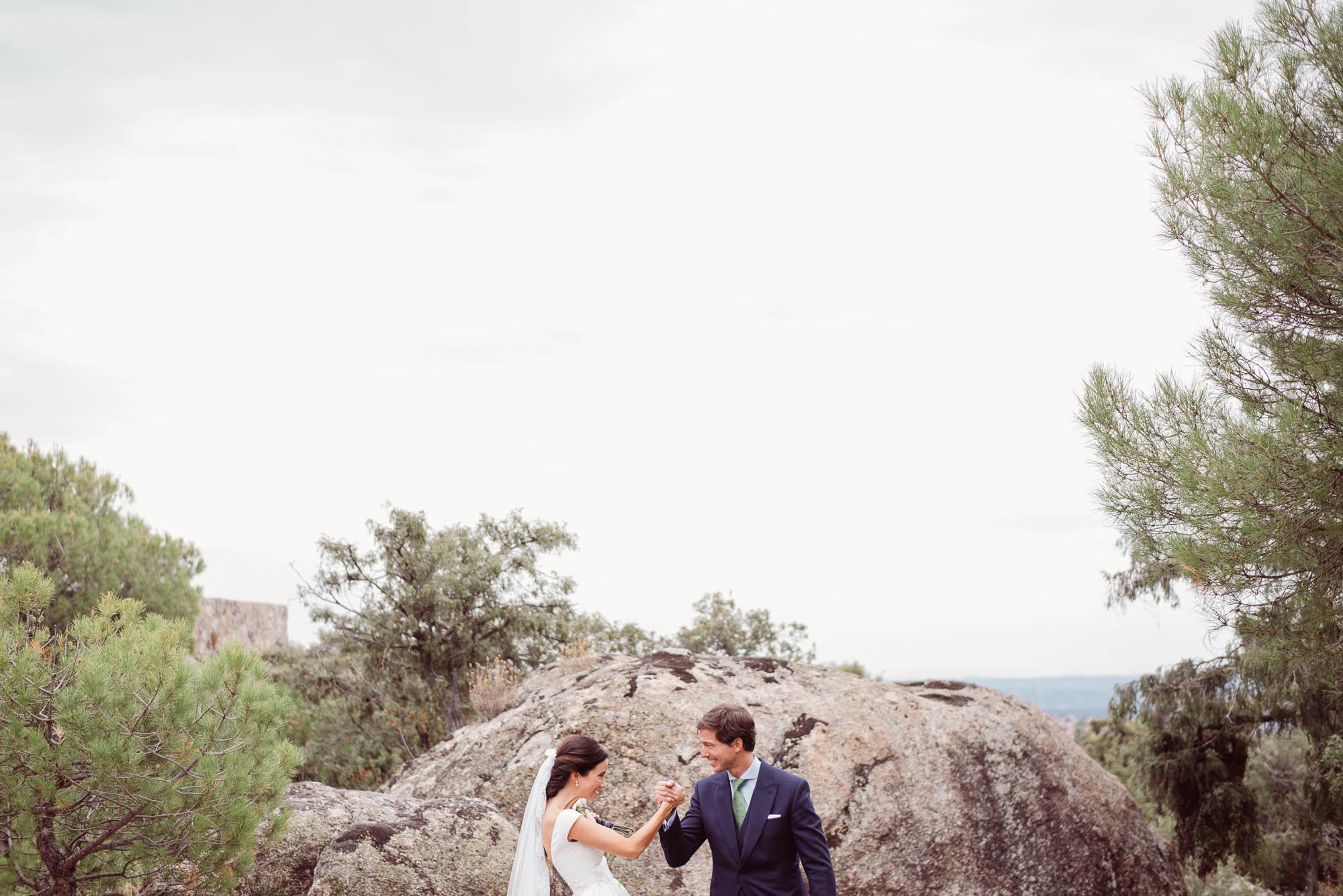 Dos novios el día de su boda con un fondo de rocas y bosque