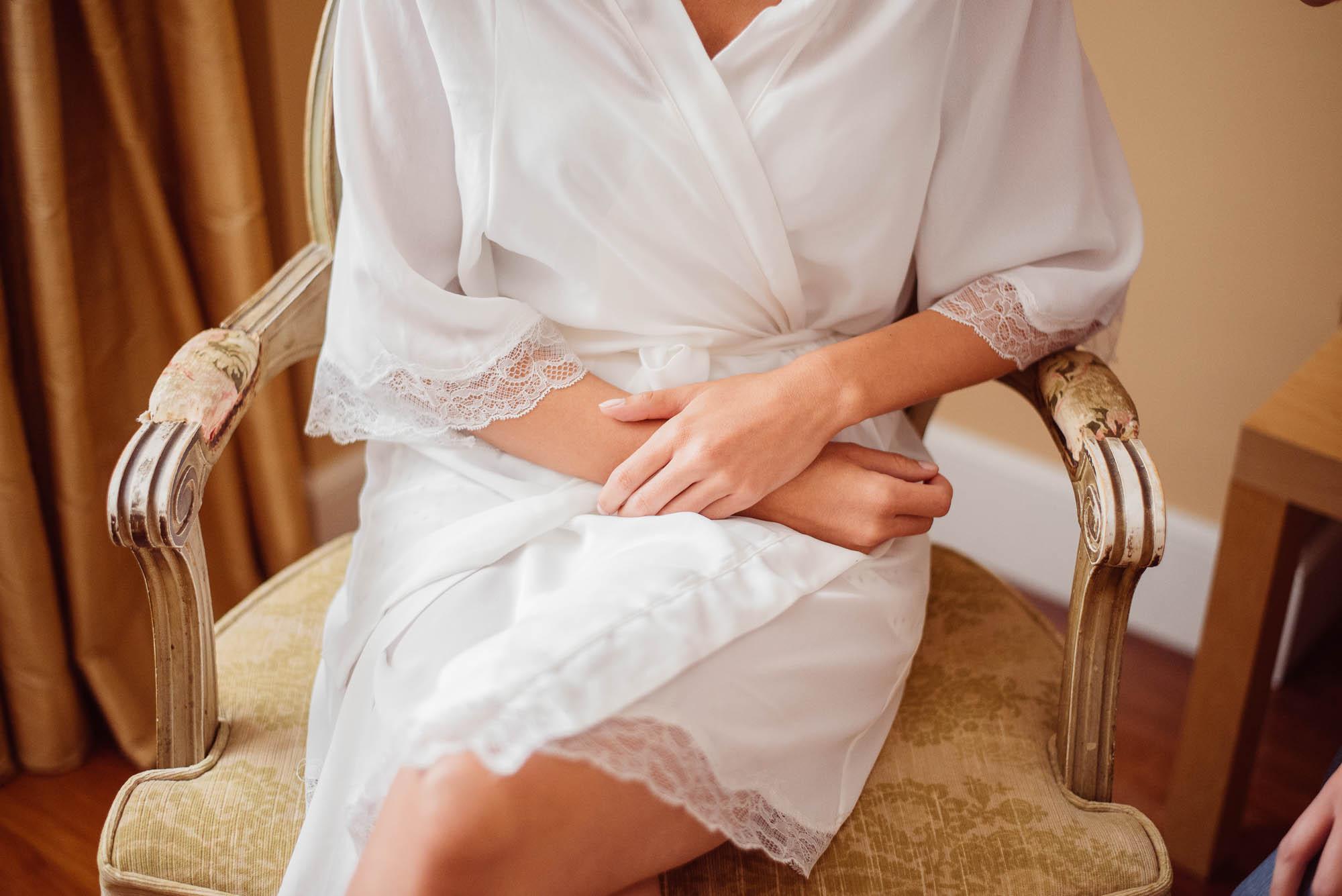 La novia esperando sentada con una bata de encaje blanco