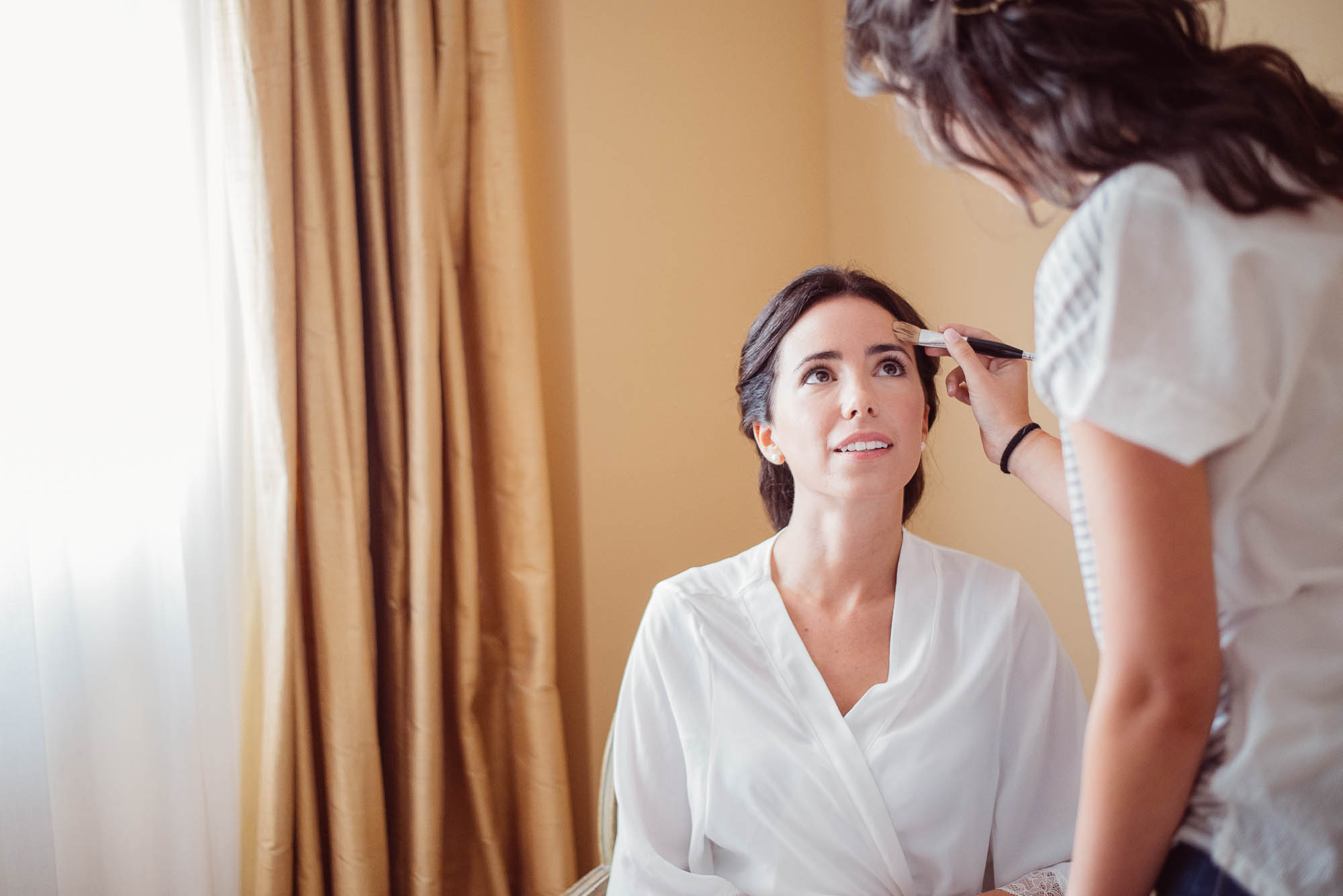 La novia maquillándose el dia de la boda