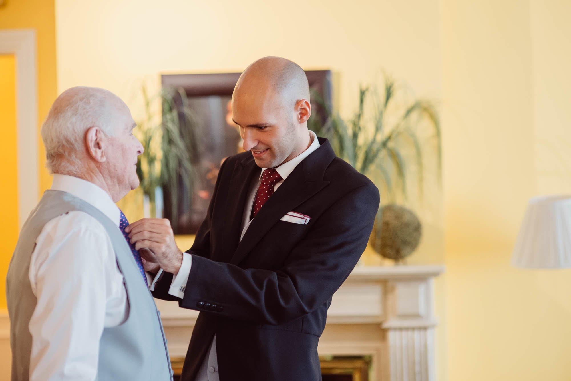 El novio arregla la corbata de su padre el dia de la boda