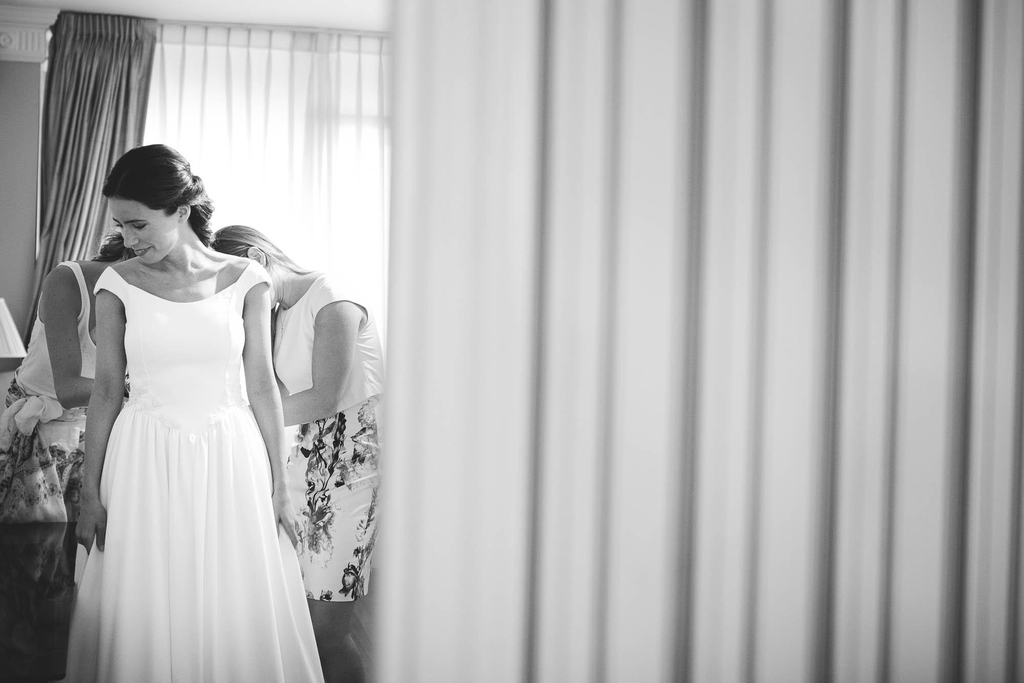 Los familiares ayudan a la novia a ponerse el vestido