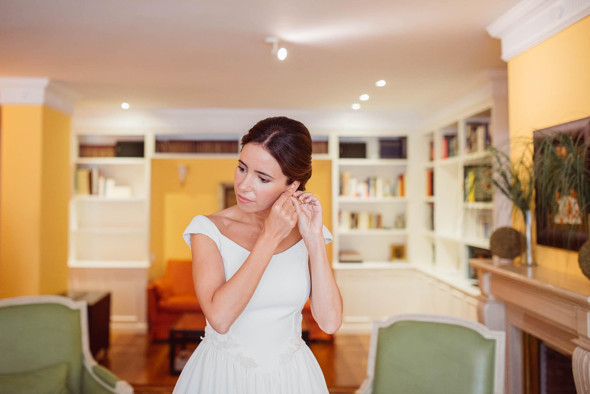 La novia se pone los pendientes en el salón de la casa