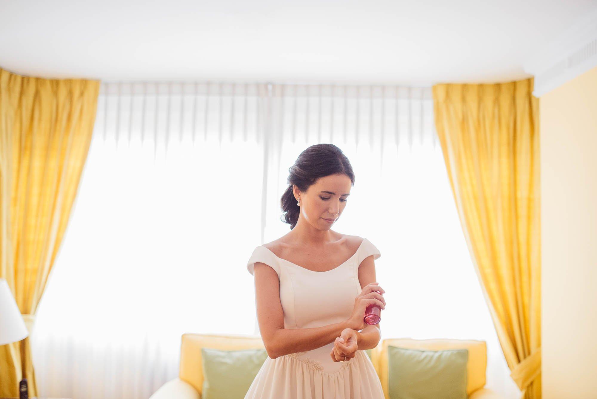 La novia se pone perfume delante del ventanal