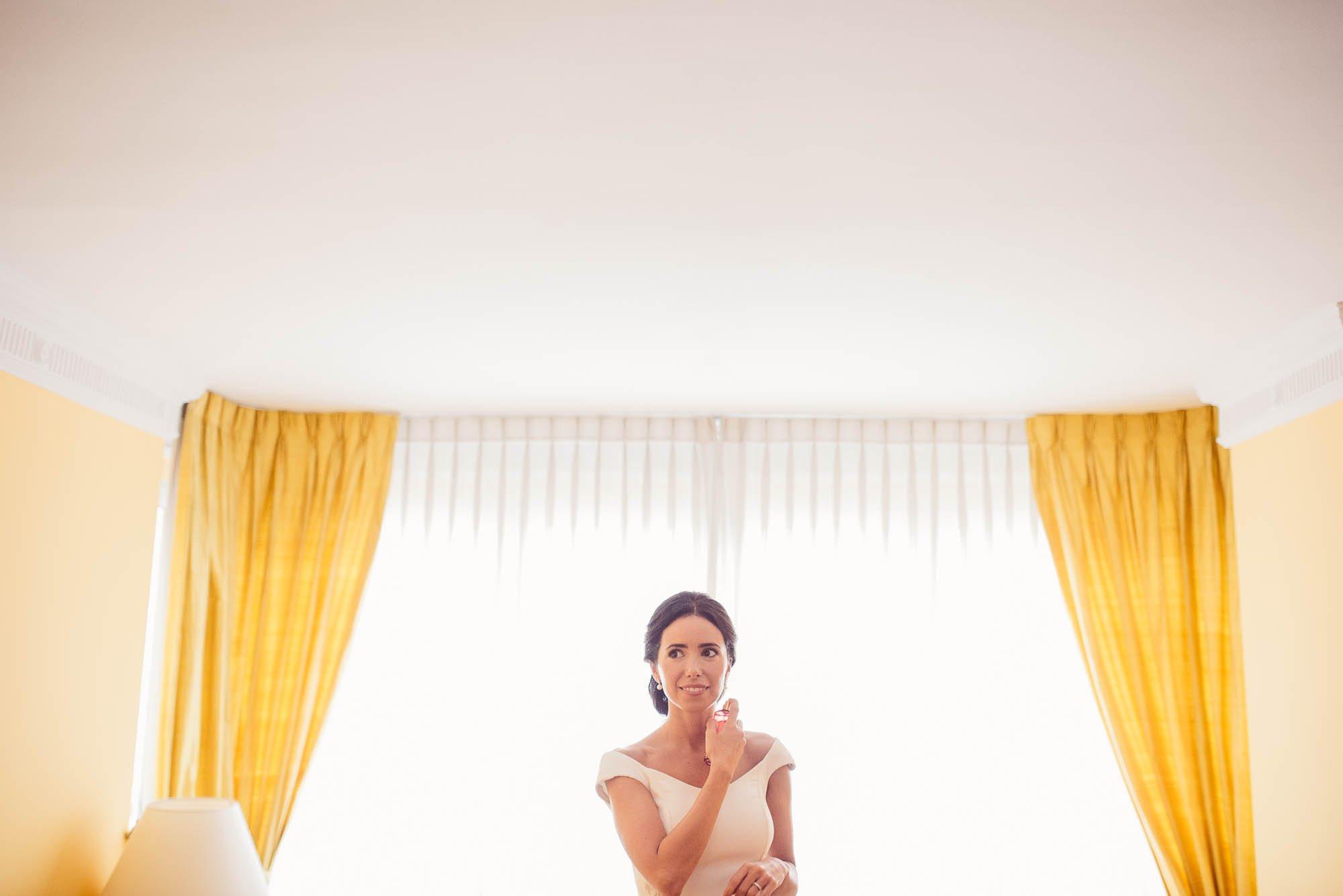 La novia se pone el perfume en el salón de su casa