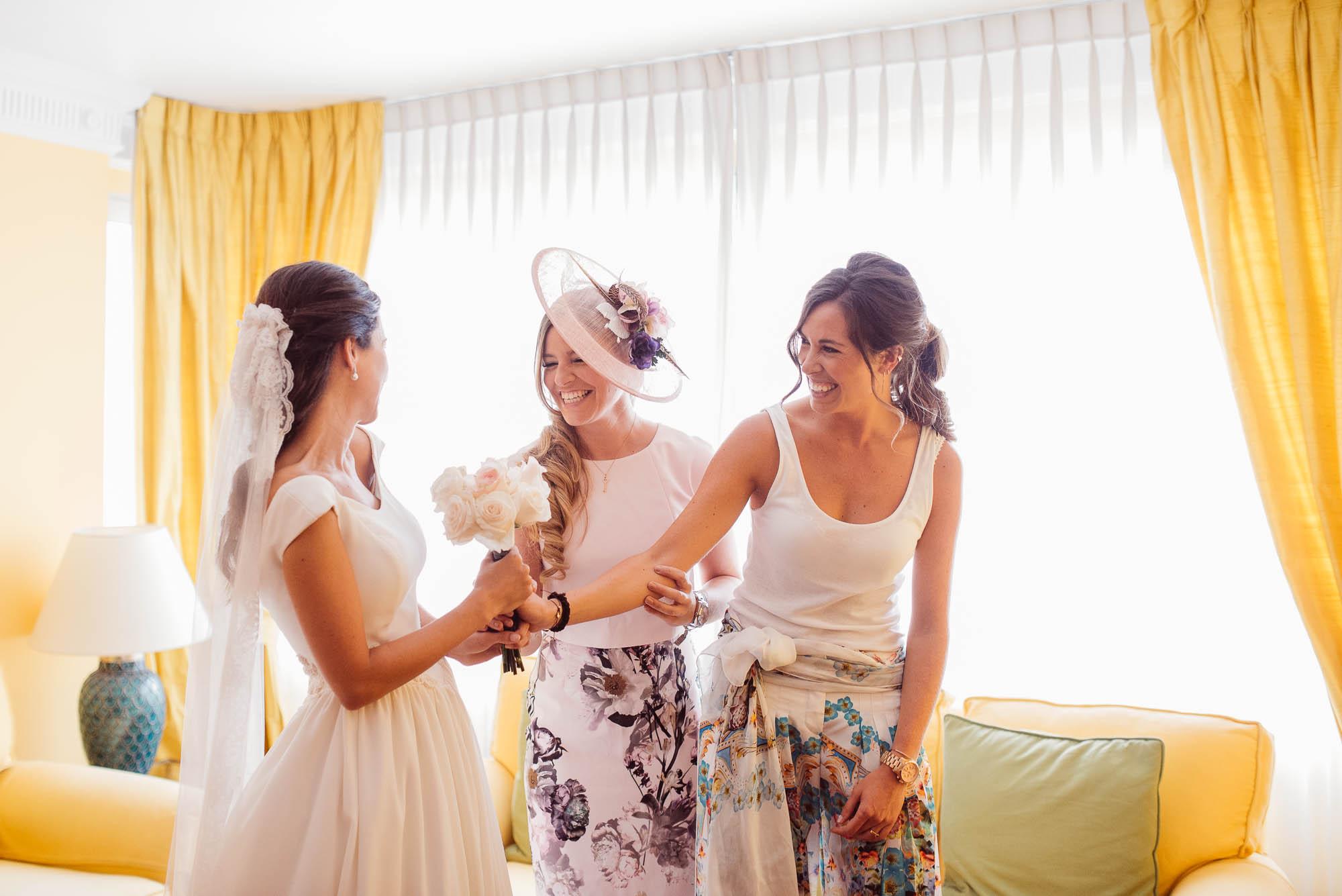 Las amigas le dan el ramo a la novia delante del ventanal