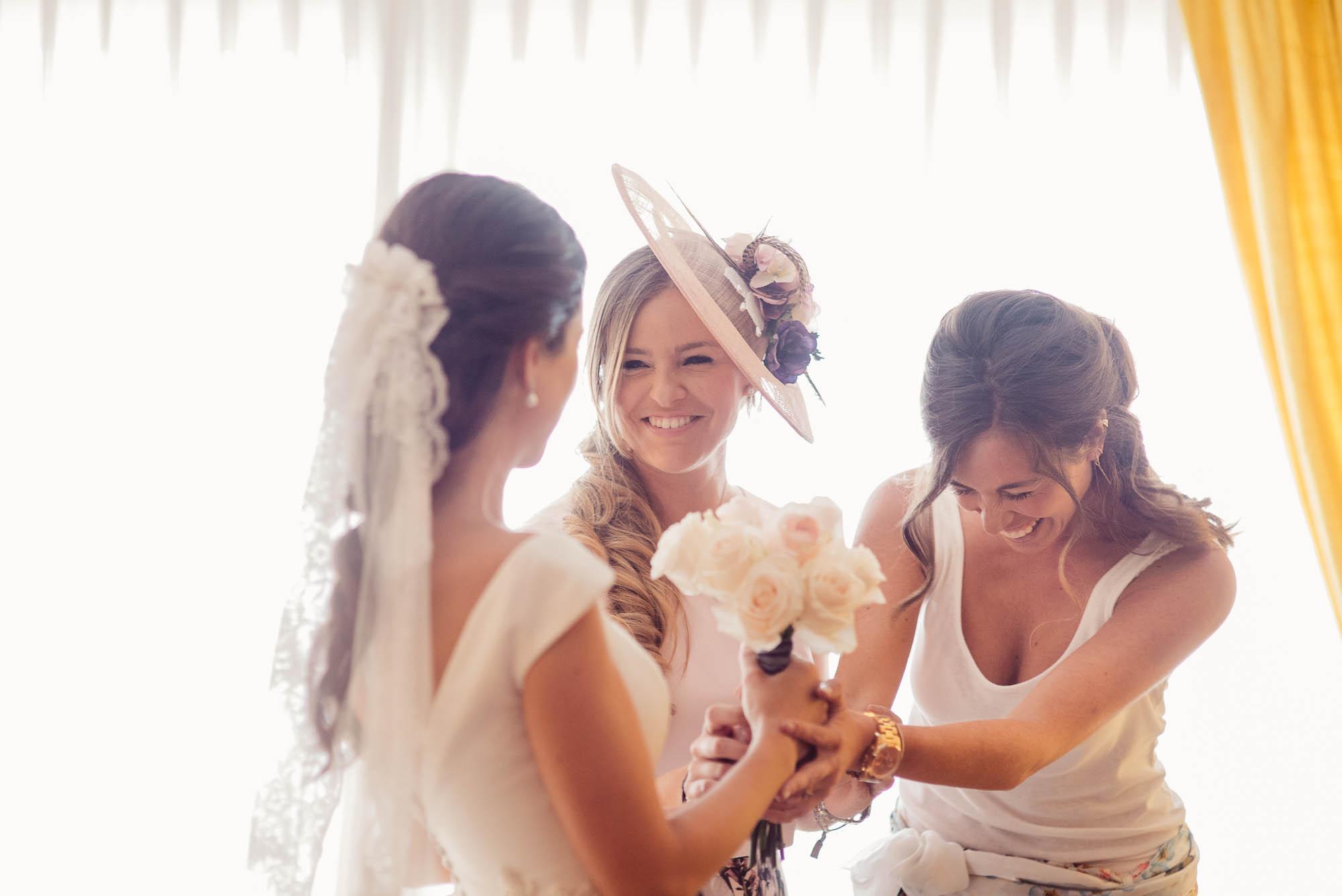 Las amigas y la novia ríen y hablan delante del ventanal