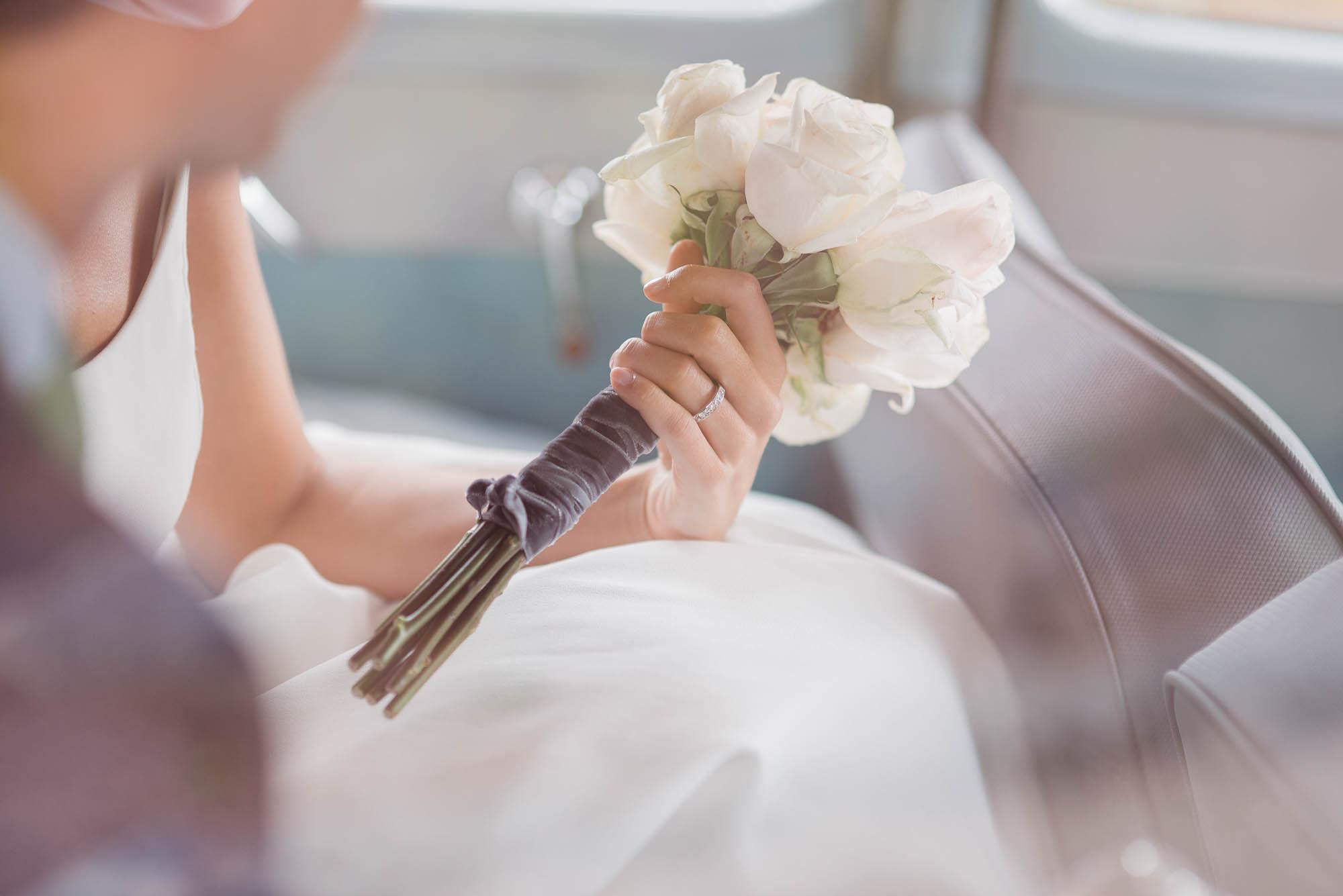 La novia sostiene el ramo blanco de bodas dentro del coche