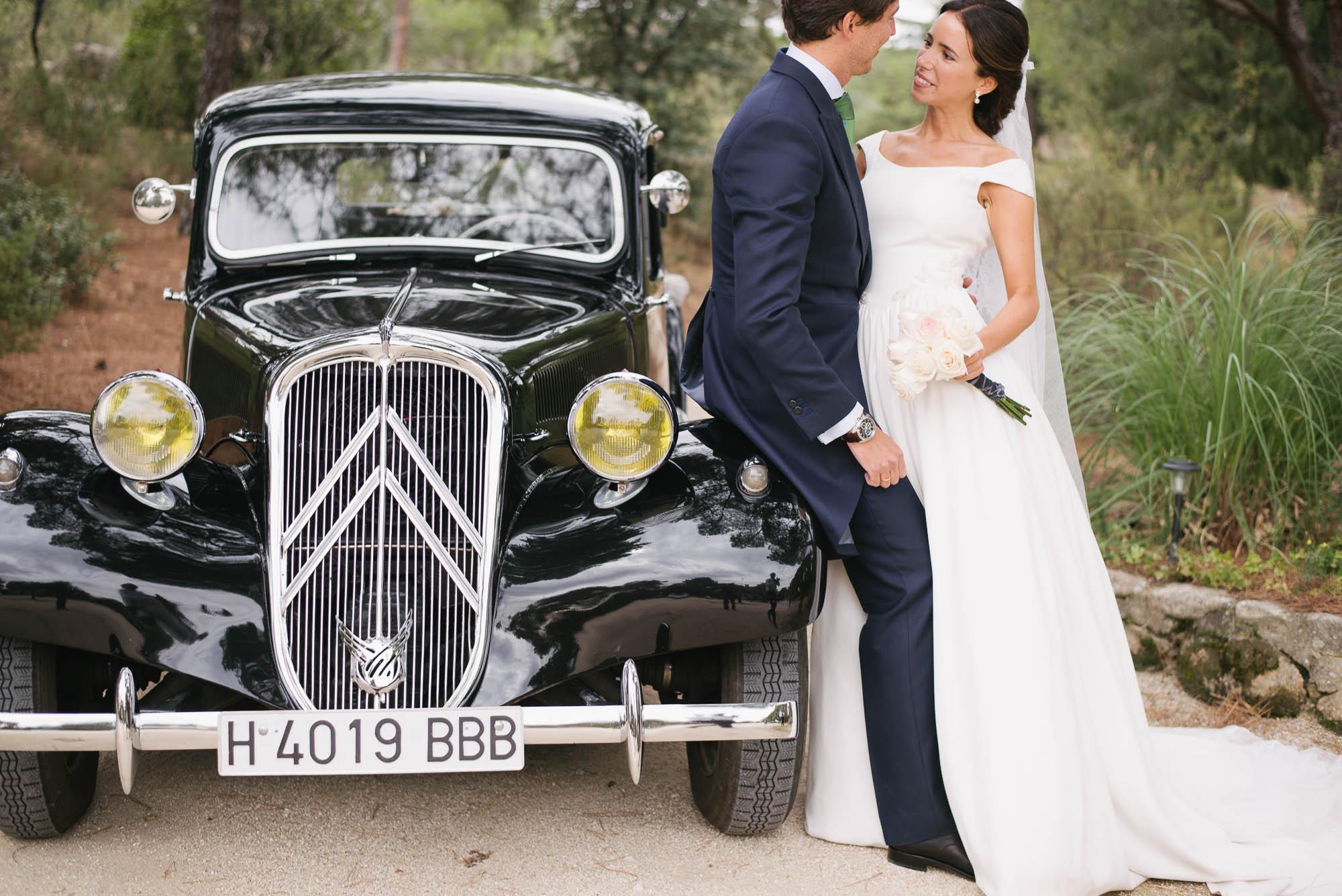 Los novios hablan junto al coche clásico el dia de la boda
