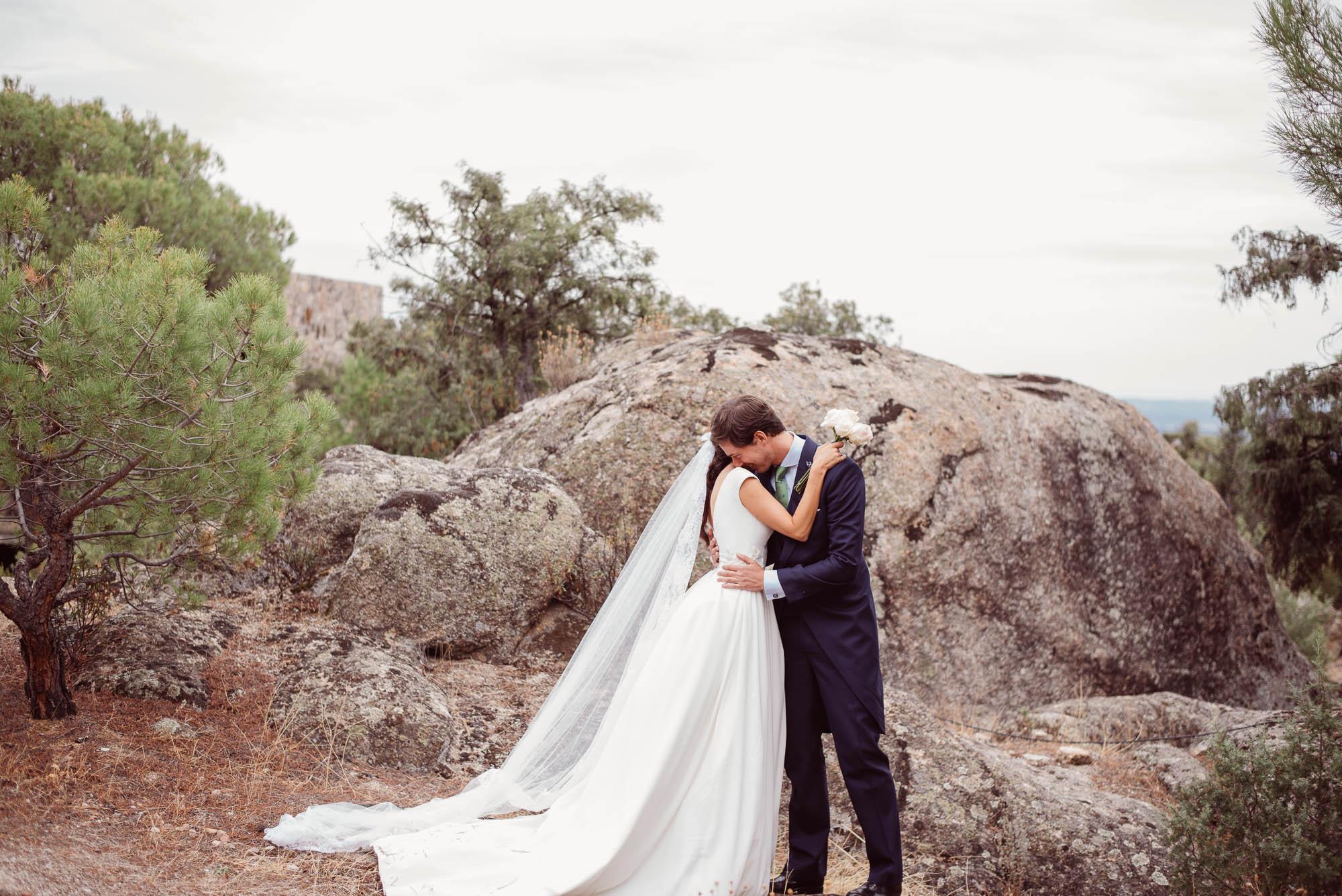 Los novios se besan delante de unas rocas llenas de vegatación