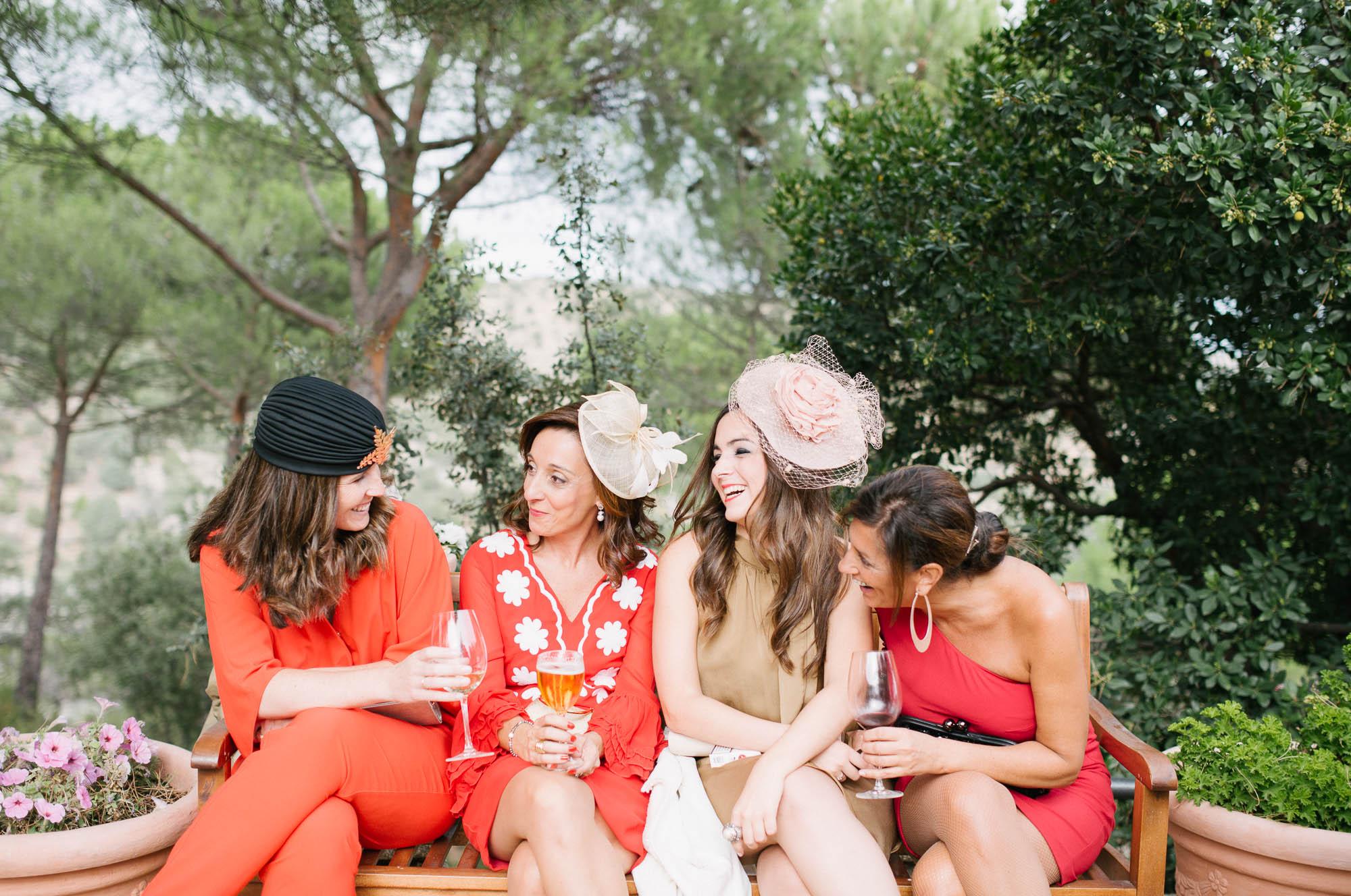 Las invitadas de rojo hablan animadamente durante el cóctel