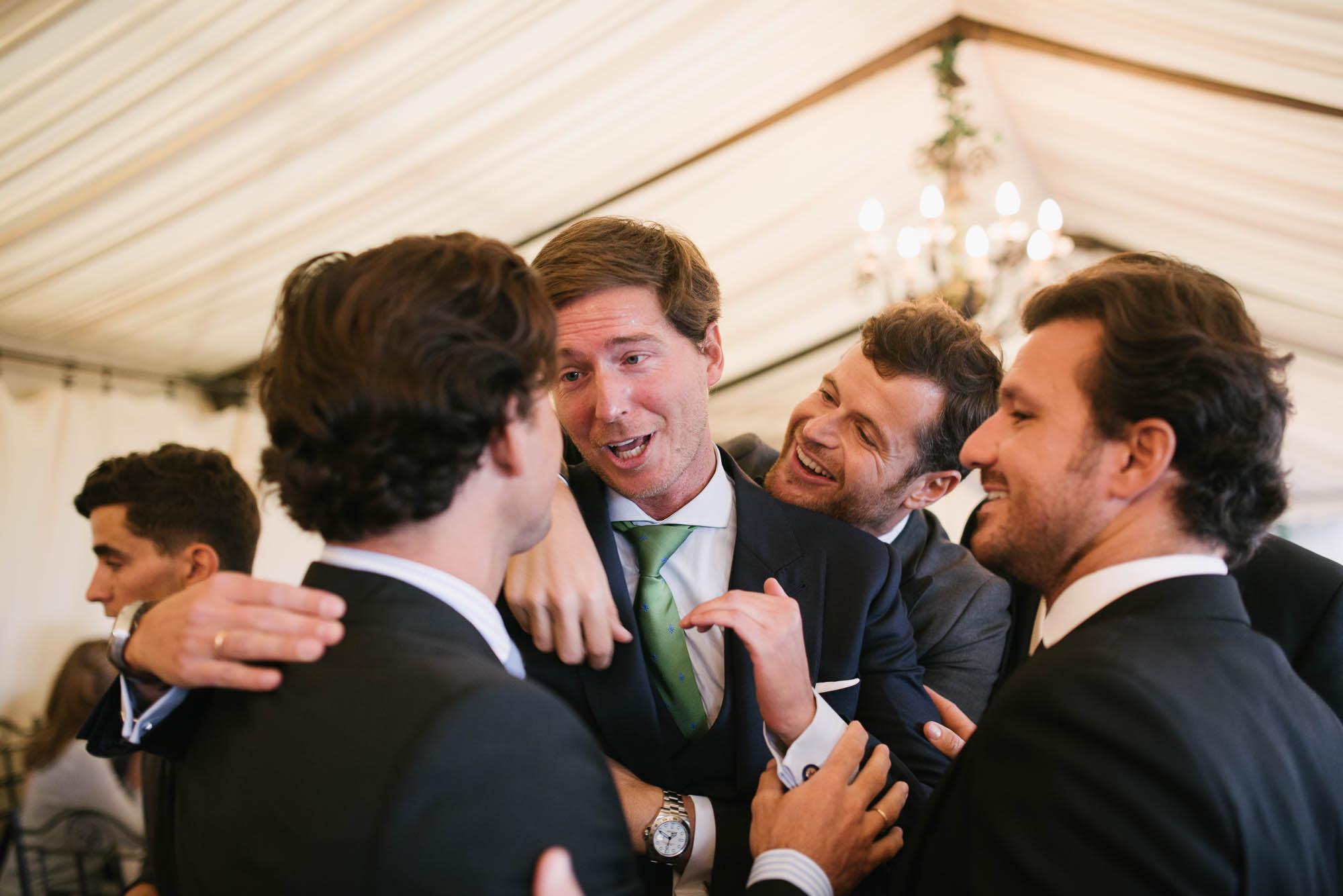 Los invitados saludan al novio en la boda