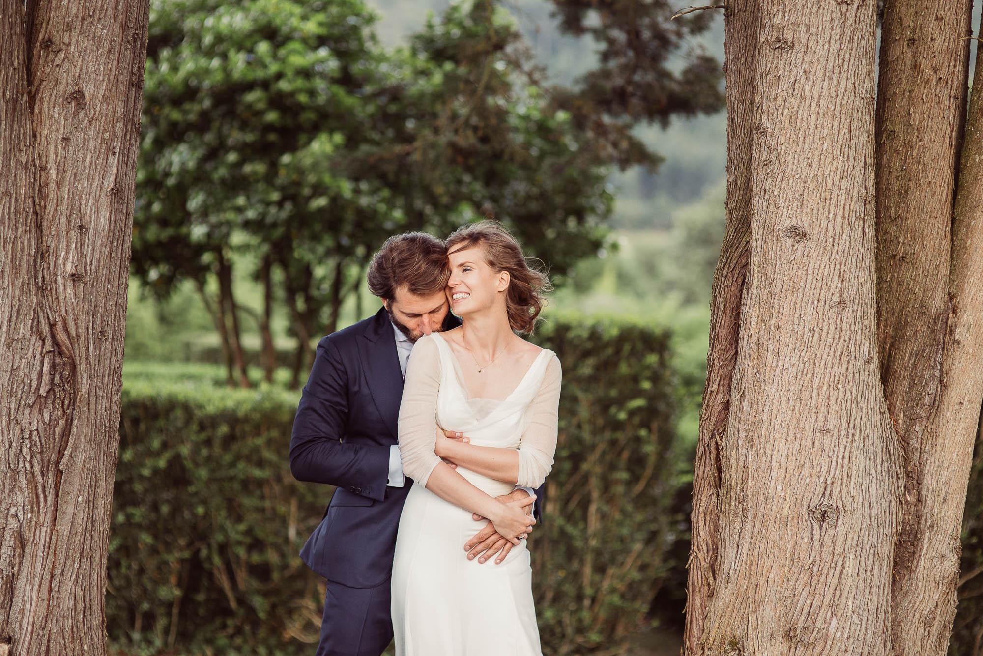 Un novio abrazando a su novia por detrás el día de su boda