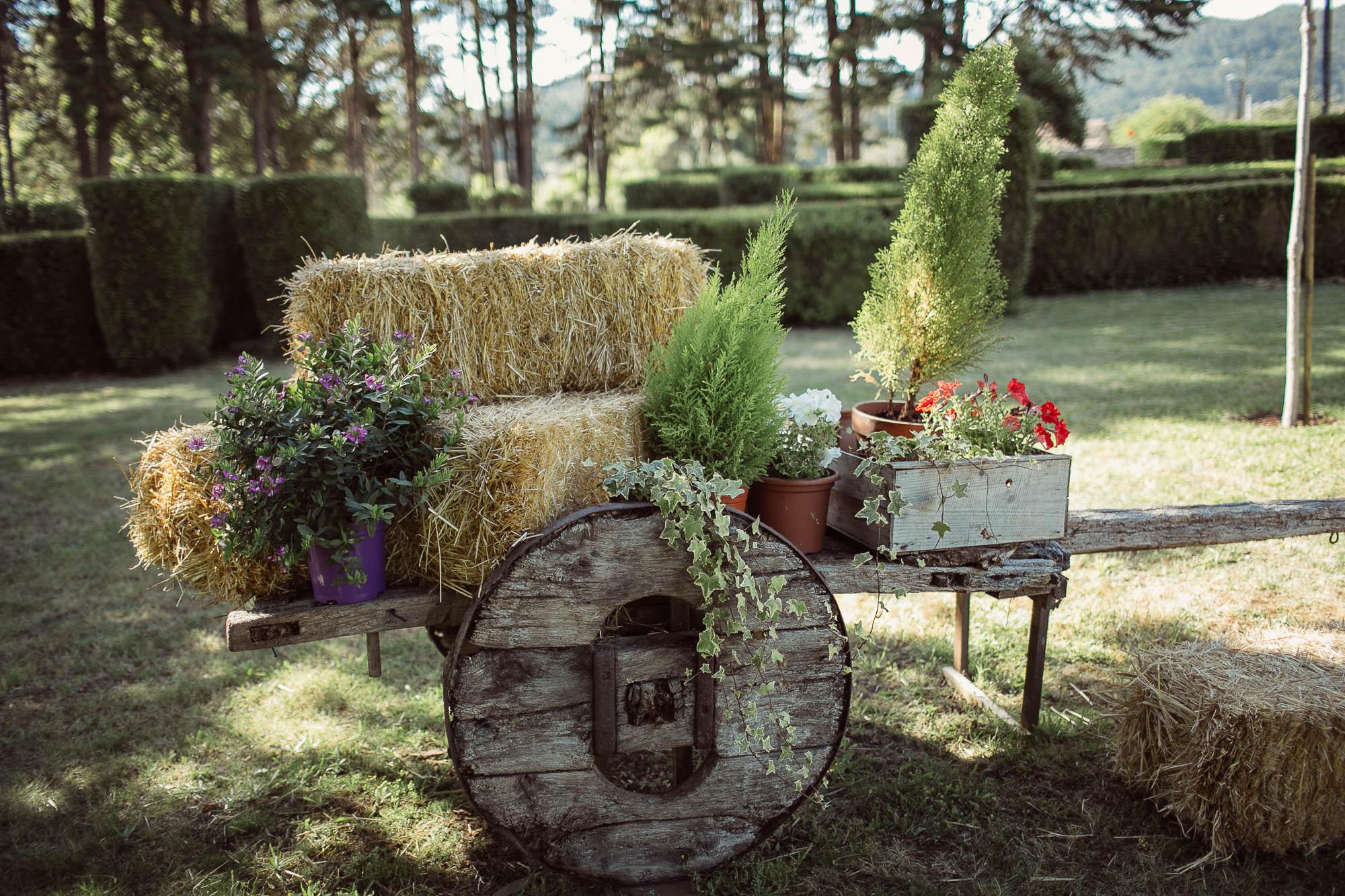 Adornos florales y vegetales de una boda sobre un carro de madera
