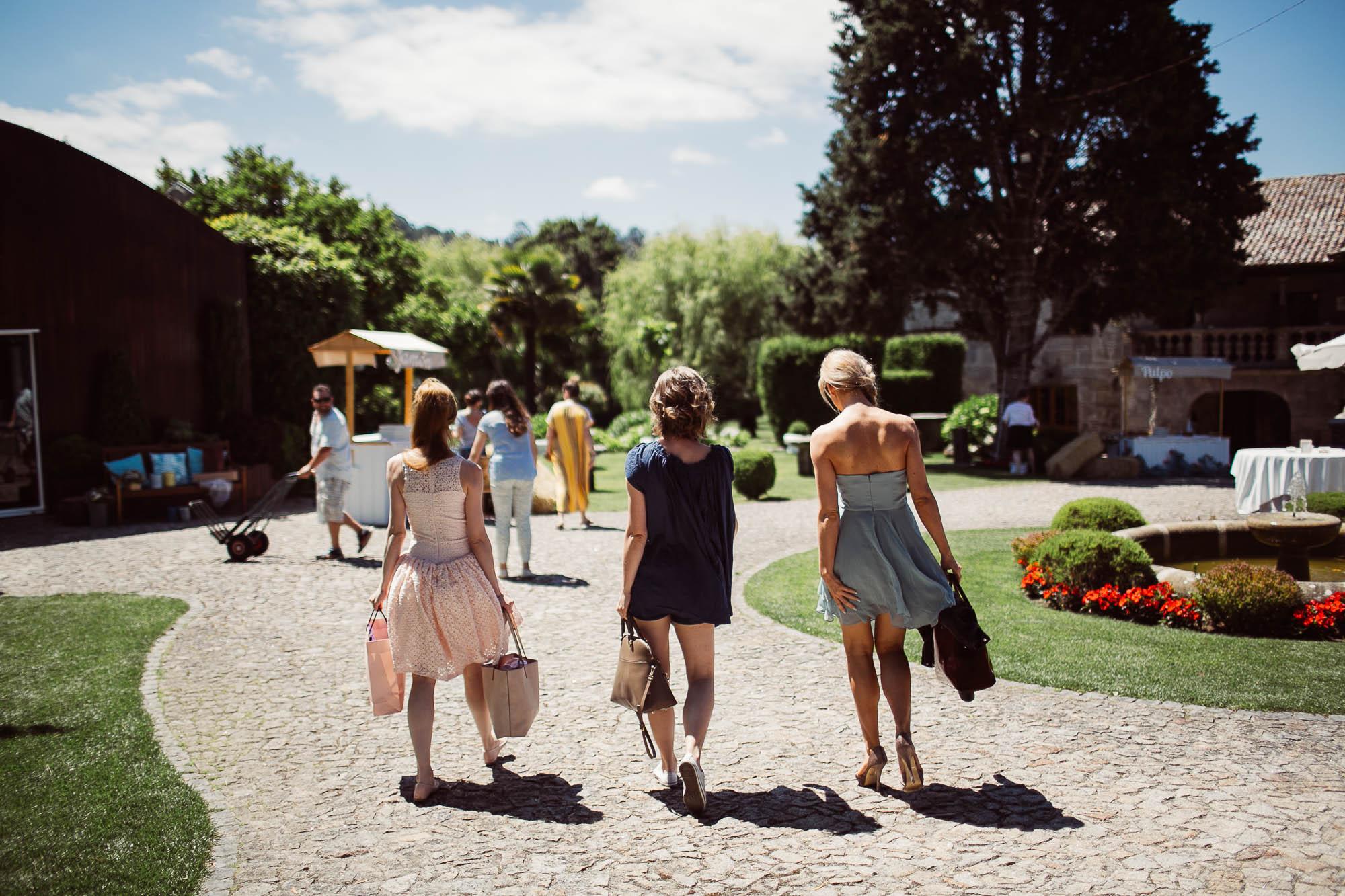 La novia y dos amigas caminando hacia su habitación para prepararse