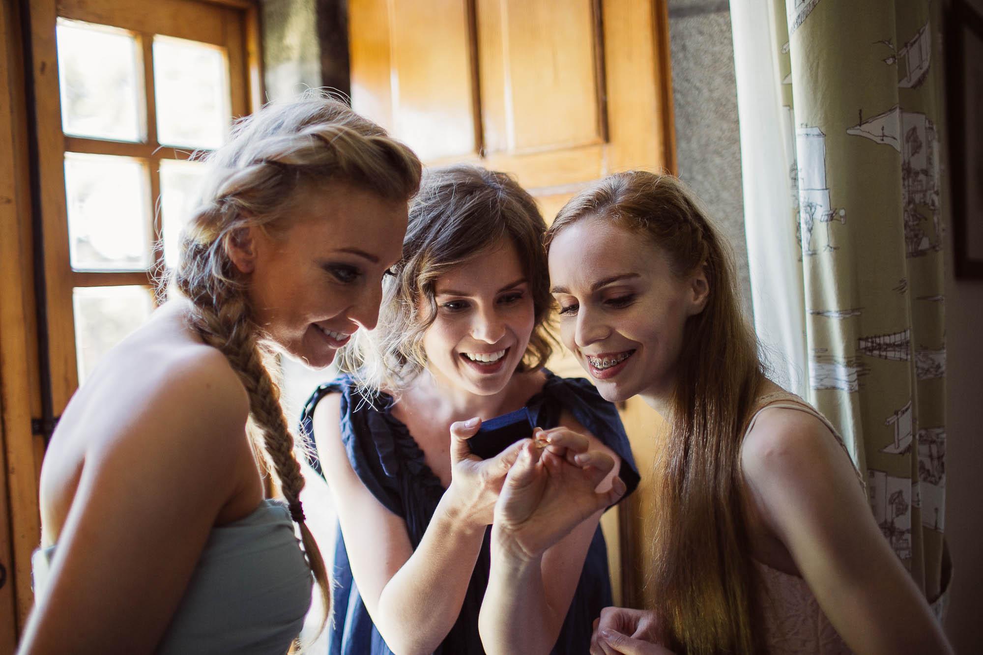 La novia y sus dos amigas viendo el anillo de compromiso
