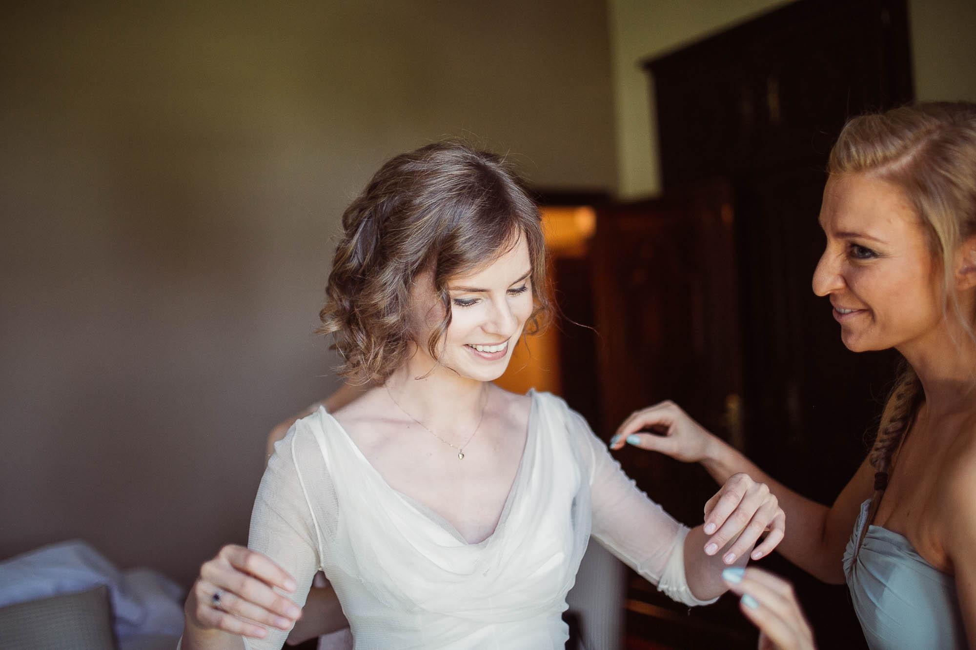 Una amiga ayudando a subir las mangas del vestido a la novia antes de la boda