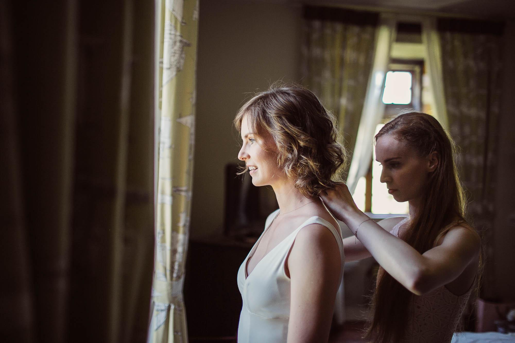 La otra amiga ayuda a la novia a subirse la tira del hombro del vestido