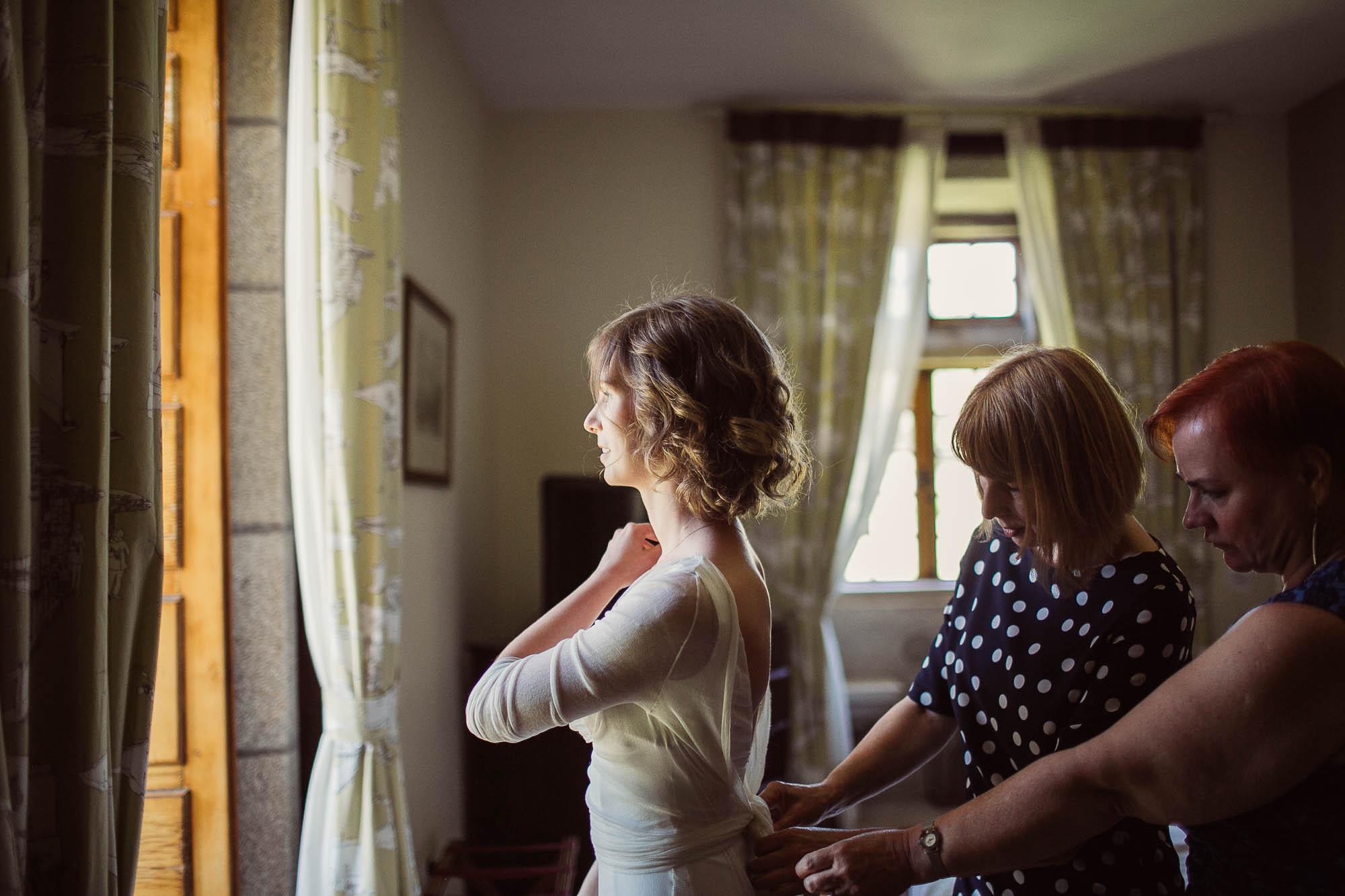 La madre de la novia y una amiga arreglando los últimos detalles del vestido frente a una ventana