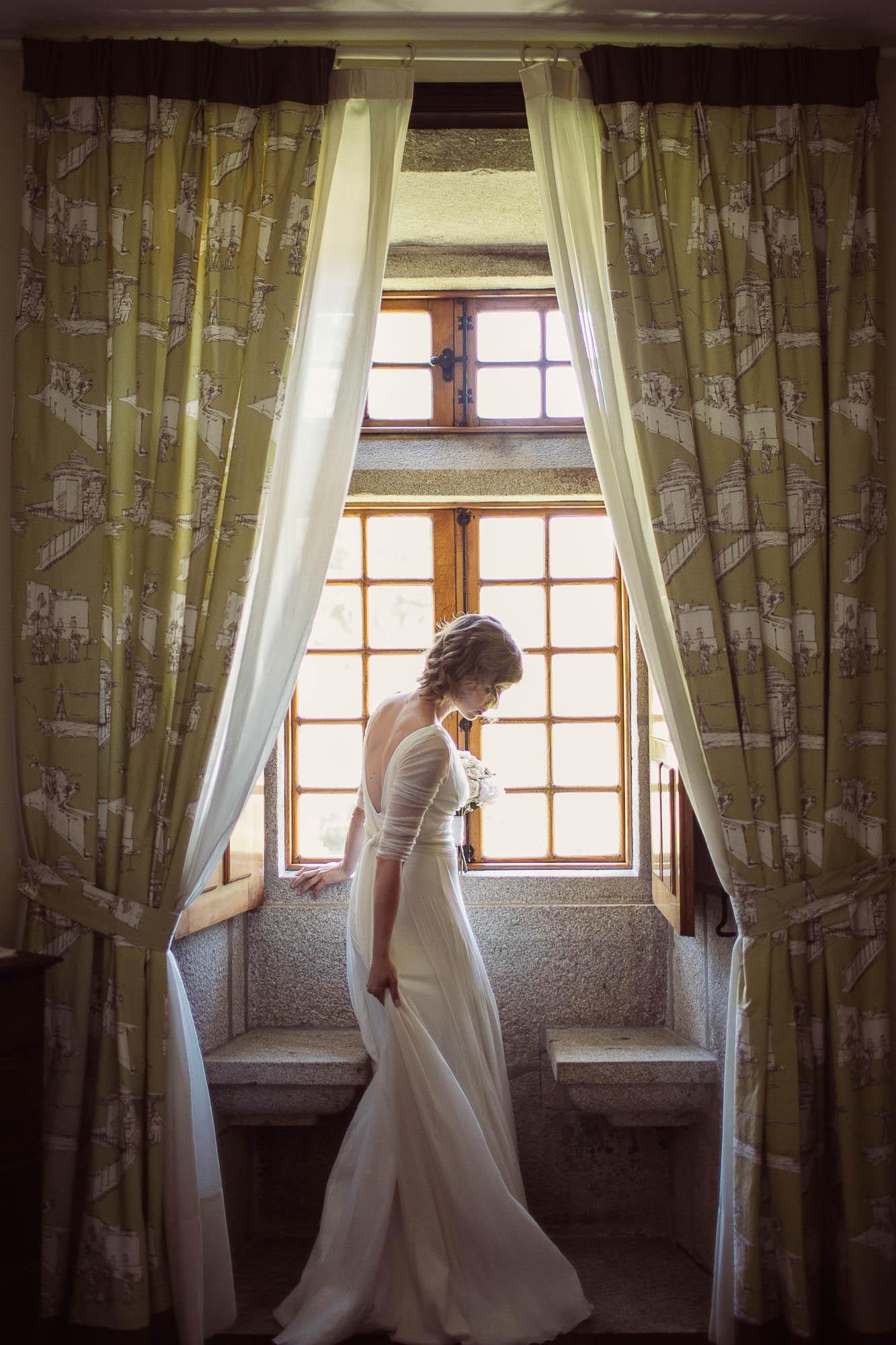 La novia, lista para salir, delante de la ventana con el ramo