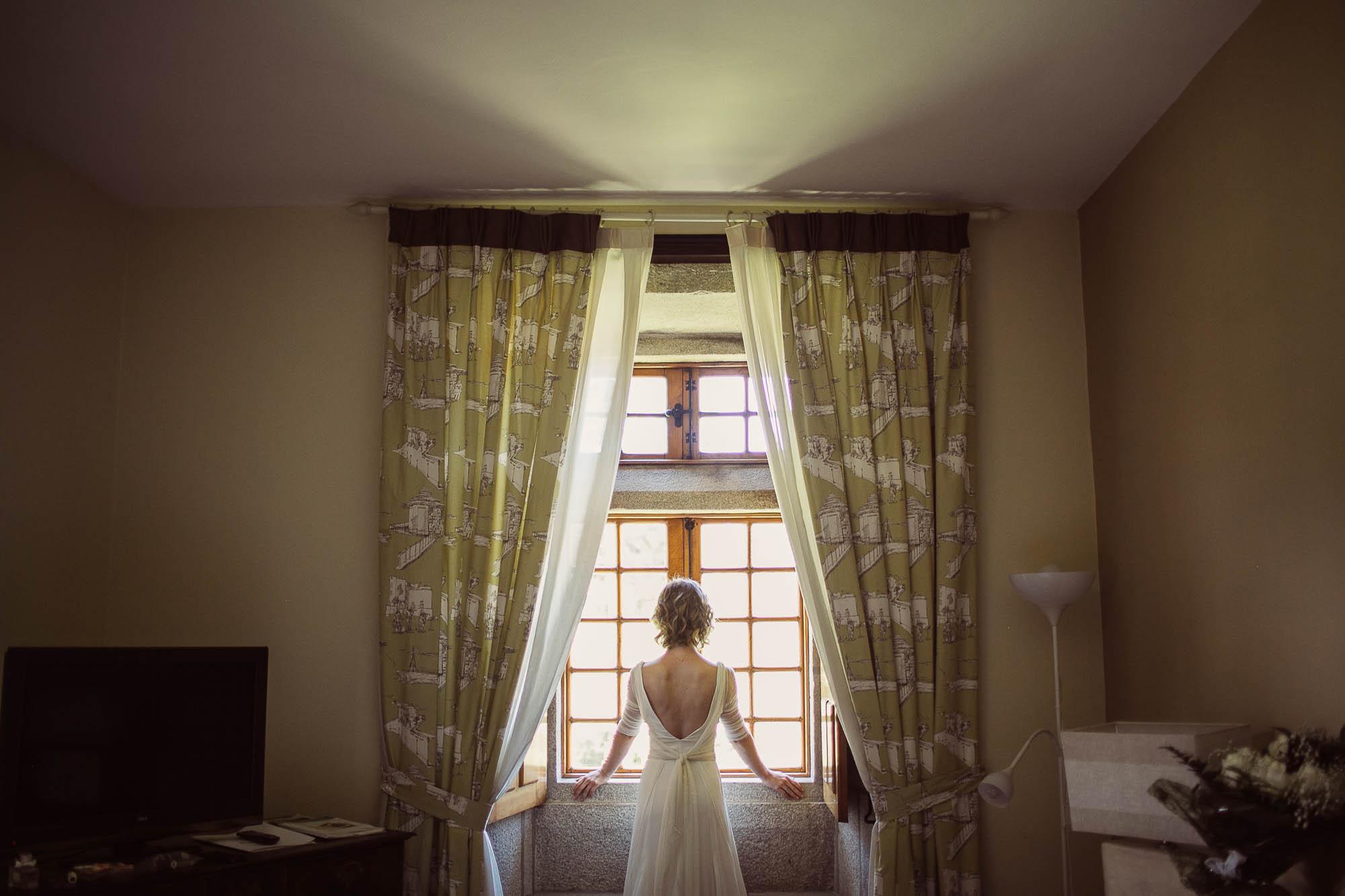 La novia mirando por la ventana antes de salir