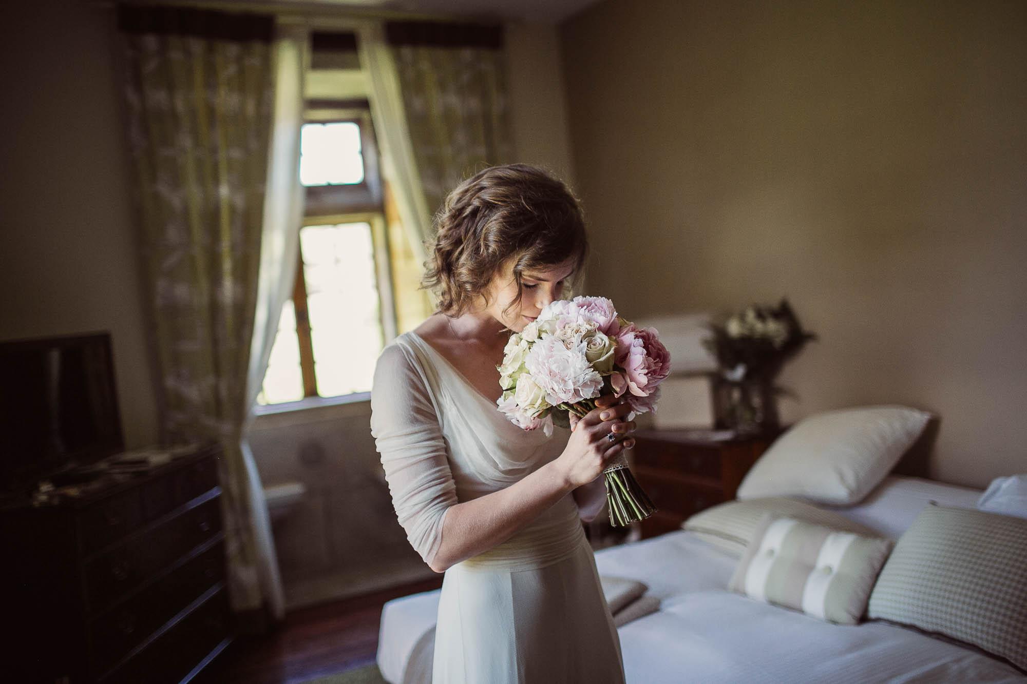 La novia oliendo el ramo de flores de boda