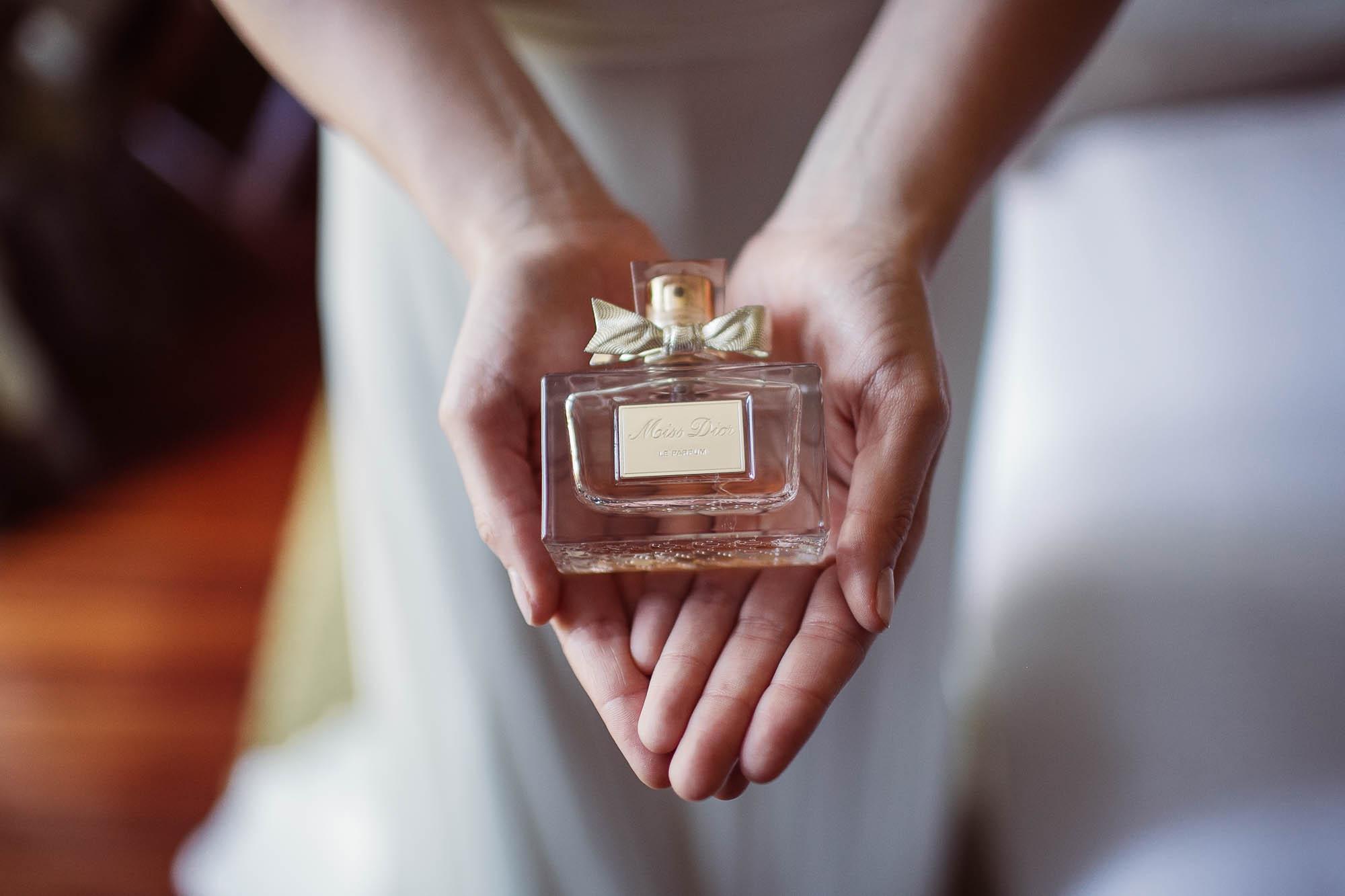 La novia sujeta el perfume sobre sus dos manos abiertas