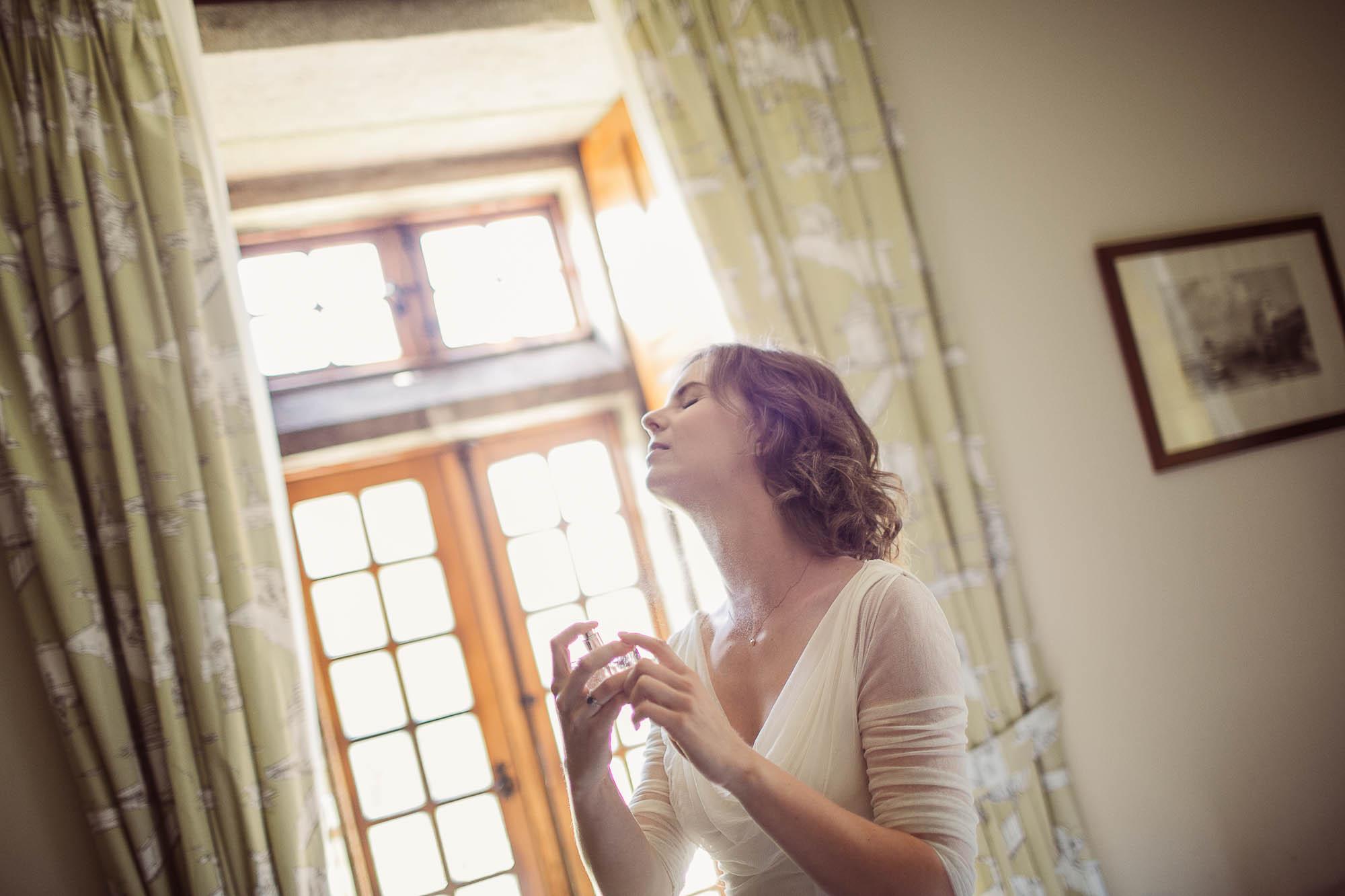 La novia se pone perfume antes de salir de la habitación