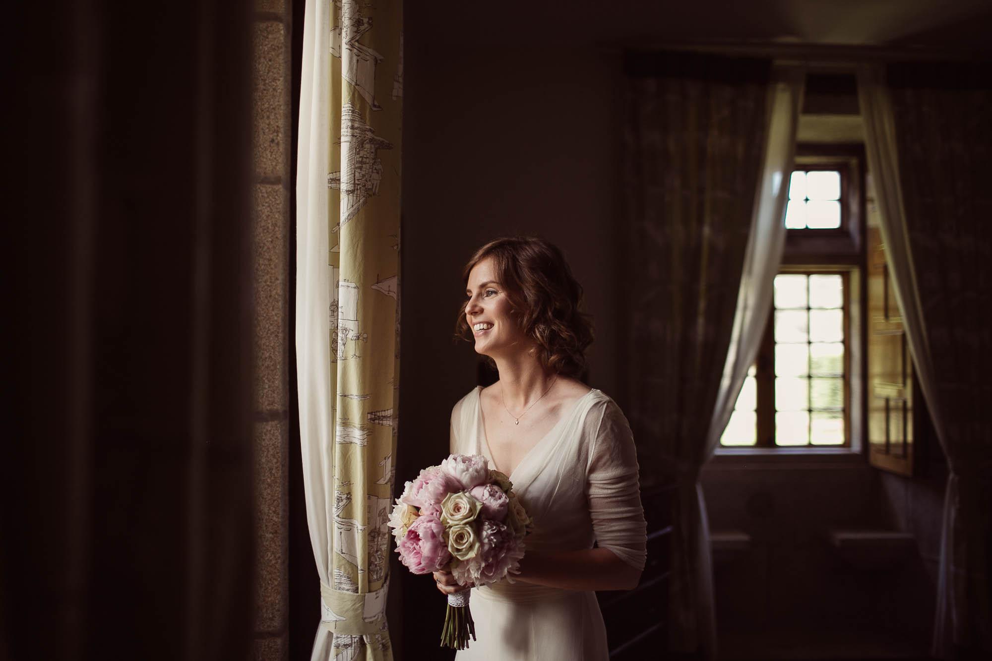 La novia mira una vez más por la ventana antes de salir hacia el altar