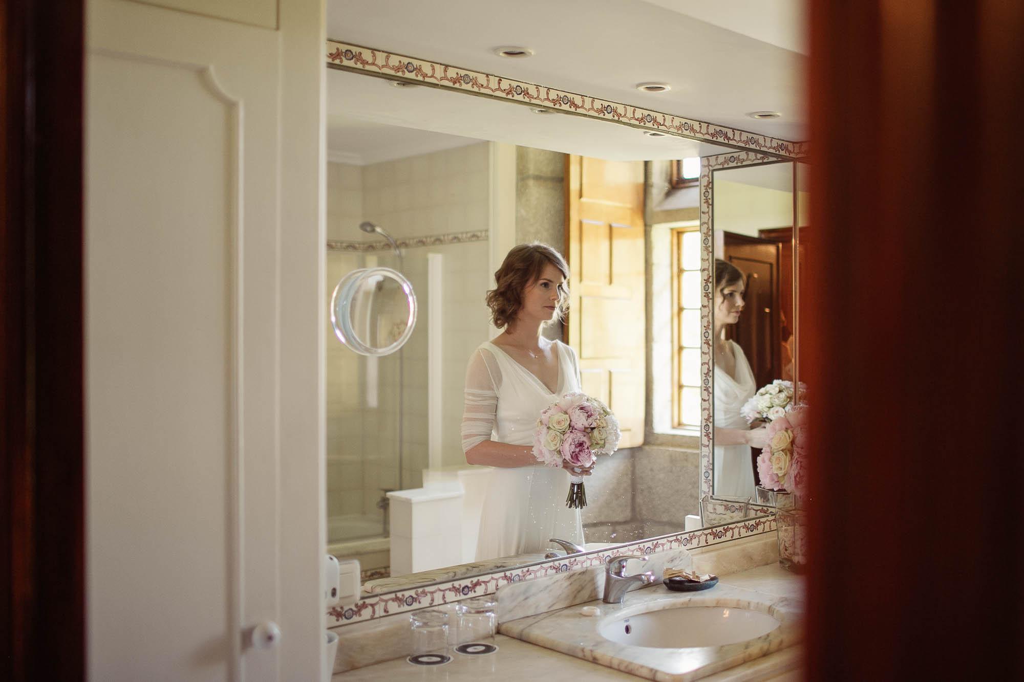 La novia se mira en el espejo del baño de su habitación antes de salir por la puerta camino al altar