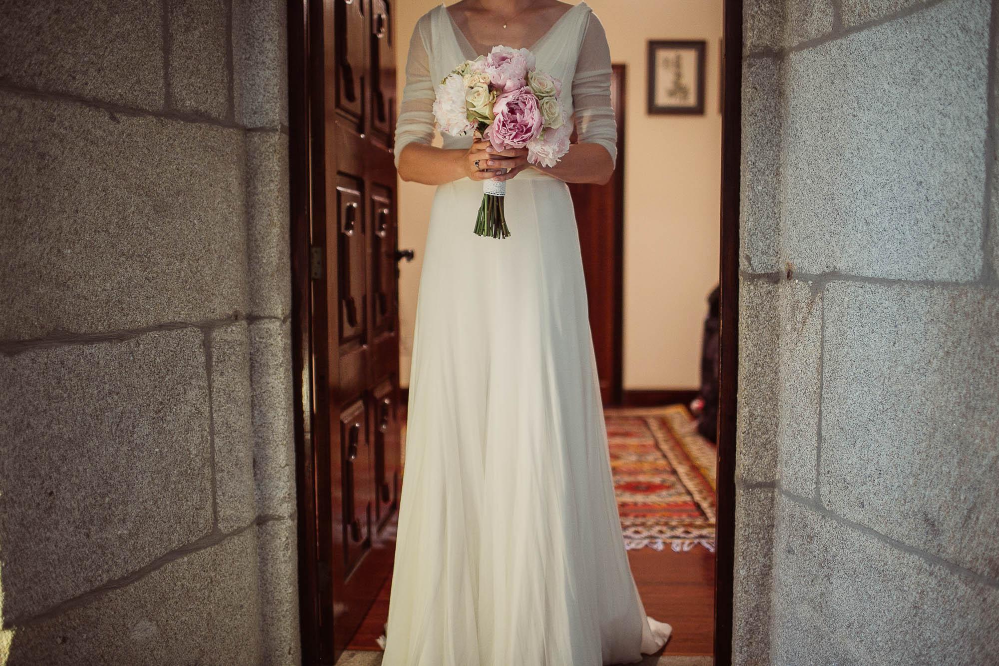 La novia sostiene el ramo de flores con las dos manos mientras sale por la puerta