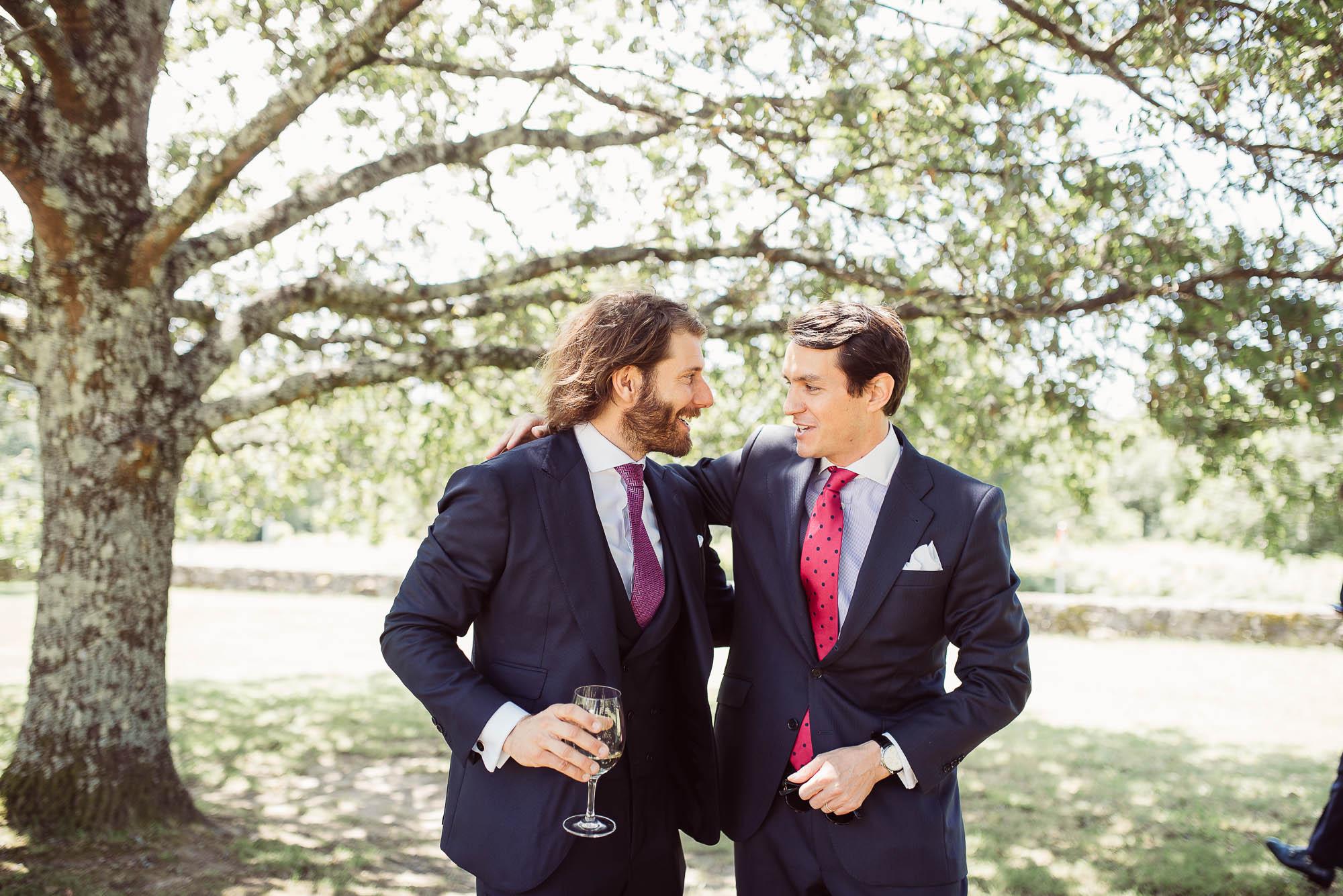 El novio sosteniendo una copa de champagne saludando a un amigo en el patio de invitados