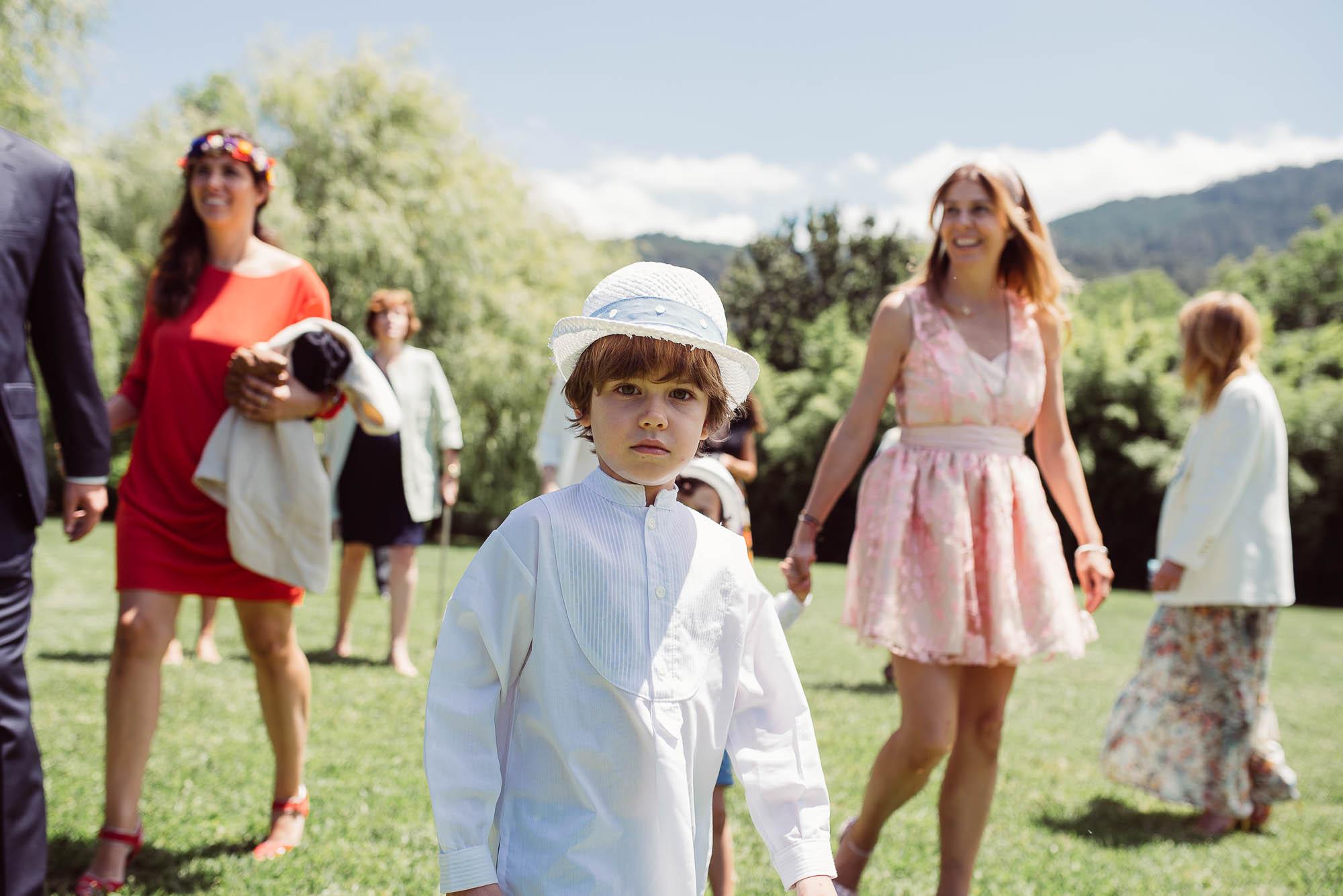 Un niño vestido de blanco con sombrero junto a varios invitados yendo de camino al altar