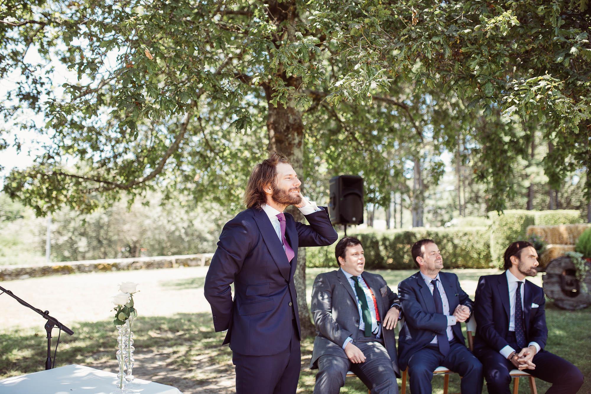 El novio sonriendo se arregla el pelo mientras espera a la novia en el altar