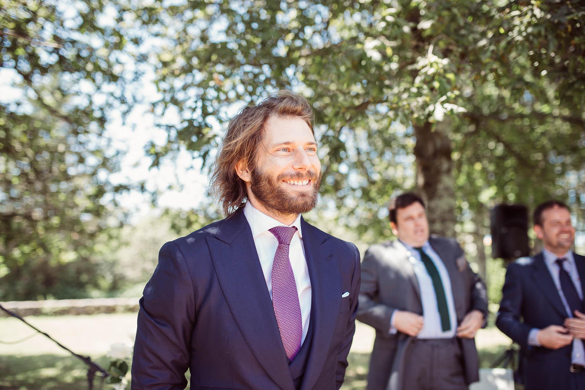 El novio sonríe emocionado al ver a la novia caminando hacia el altar