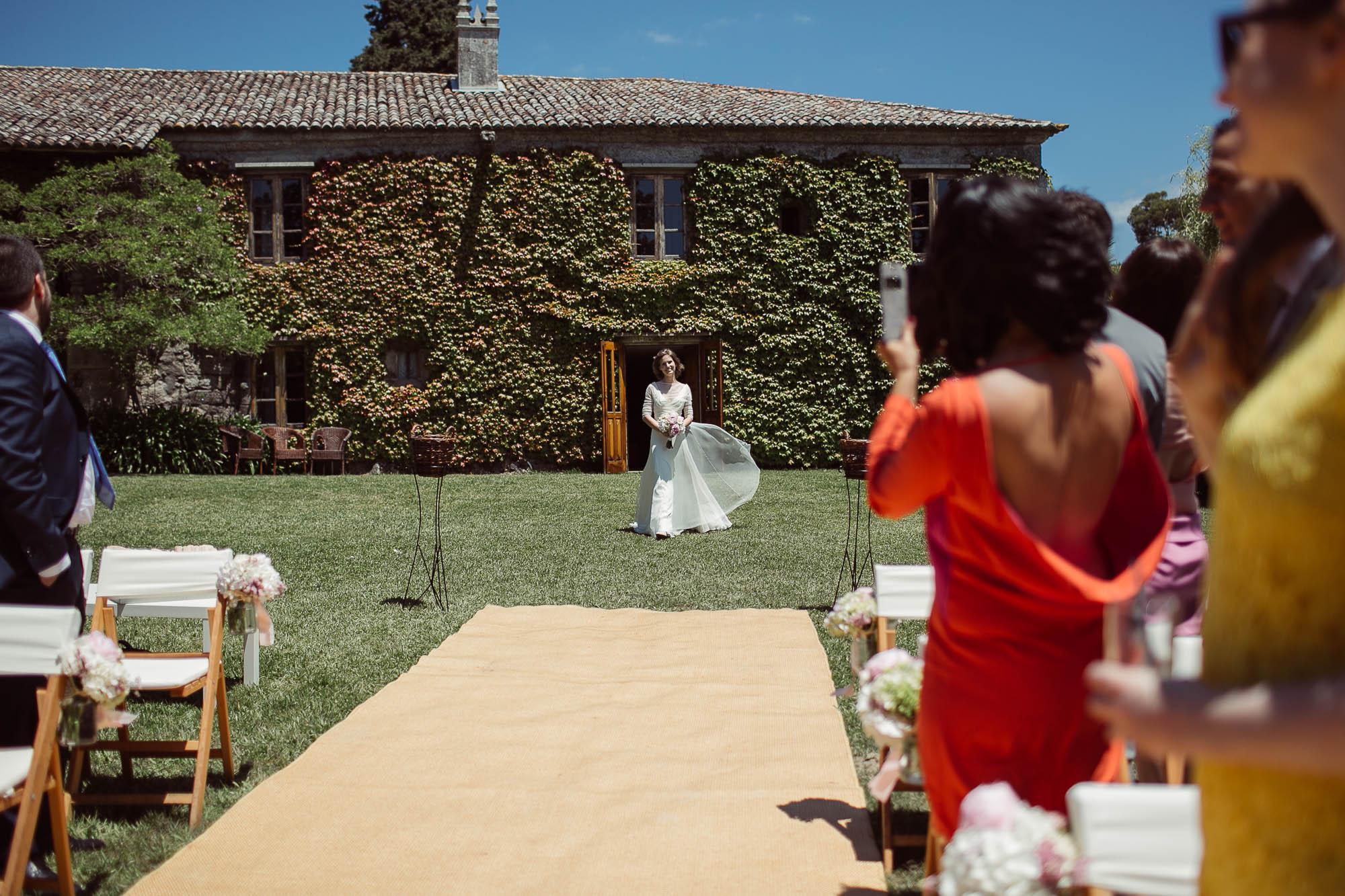 La novia se ve caminando hacia el altar mientras los invitados se giran emocionados y le sacan fotografías