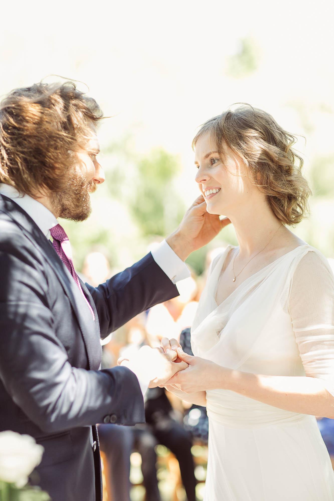La novia poniéndole el anillo al novio mientras se miran a la cara