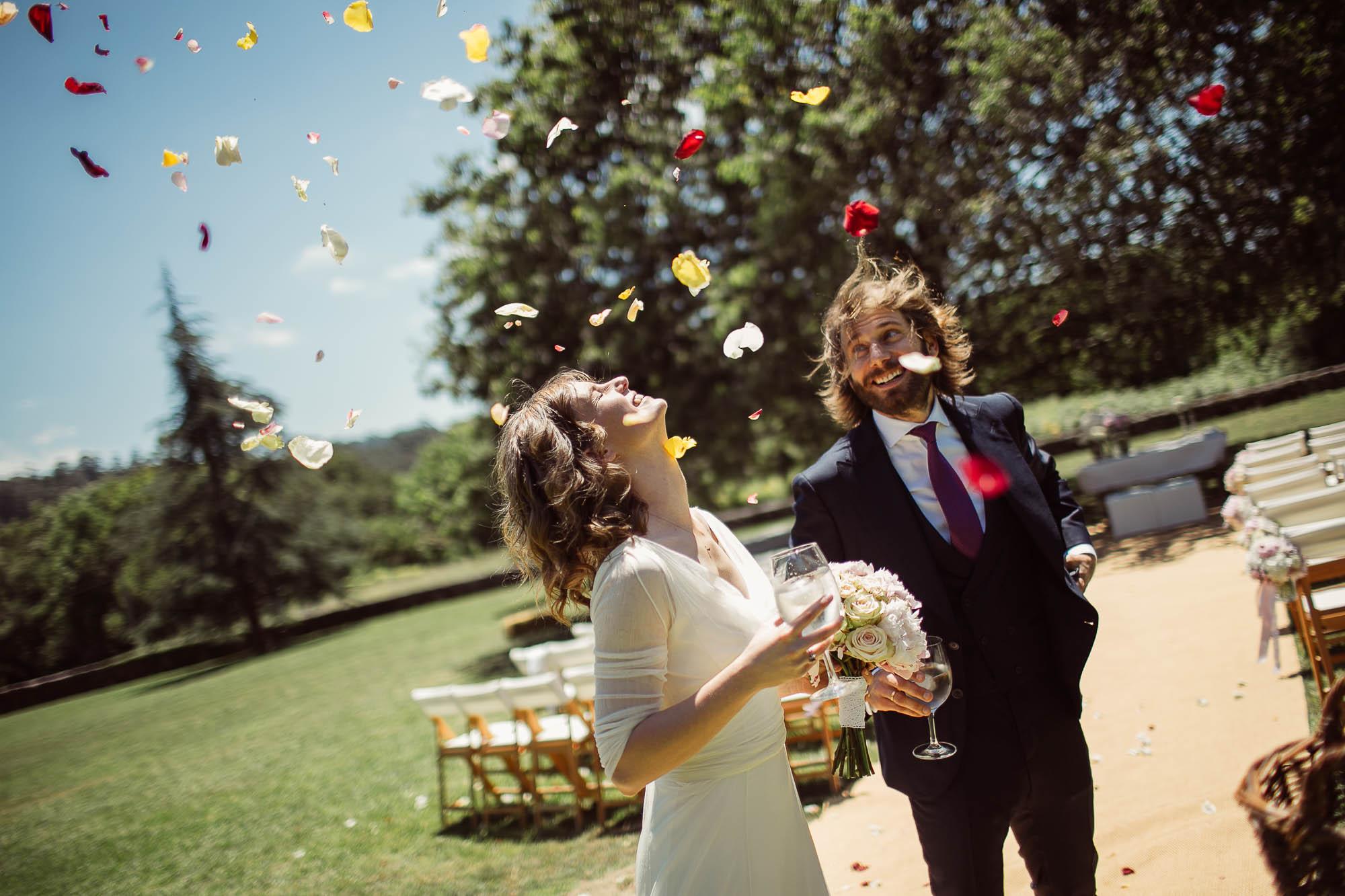 Los novios con una copa en la mano mientras llueven pétalos de flores