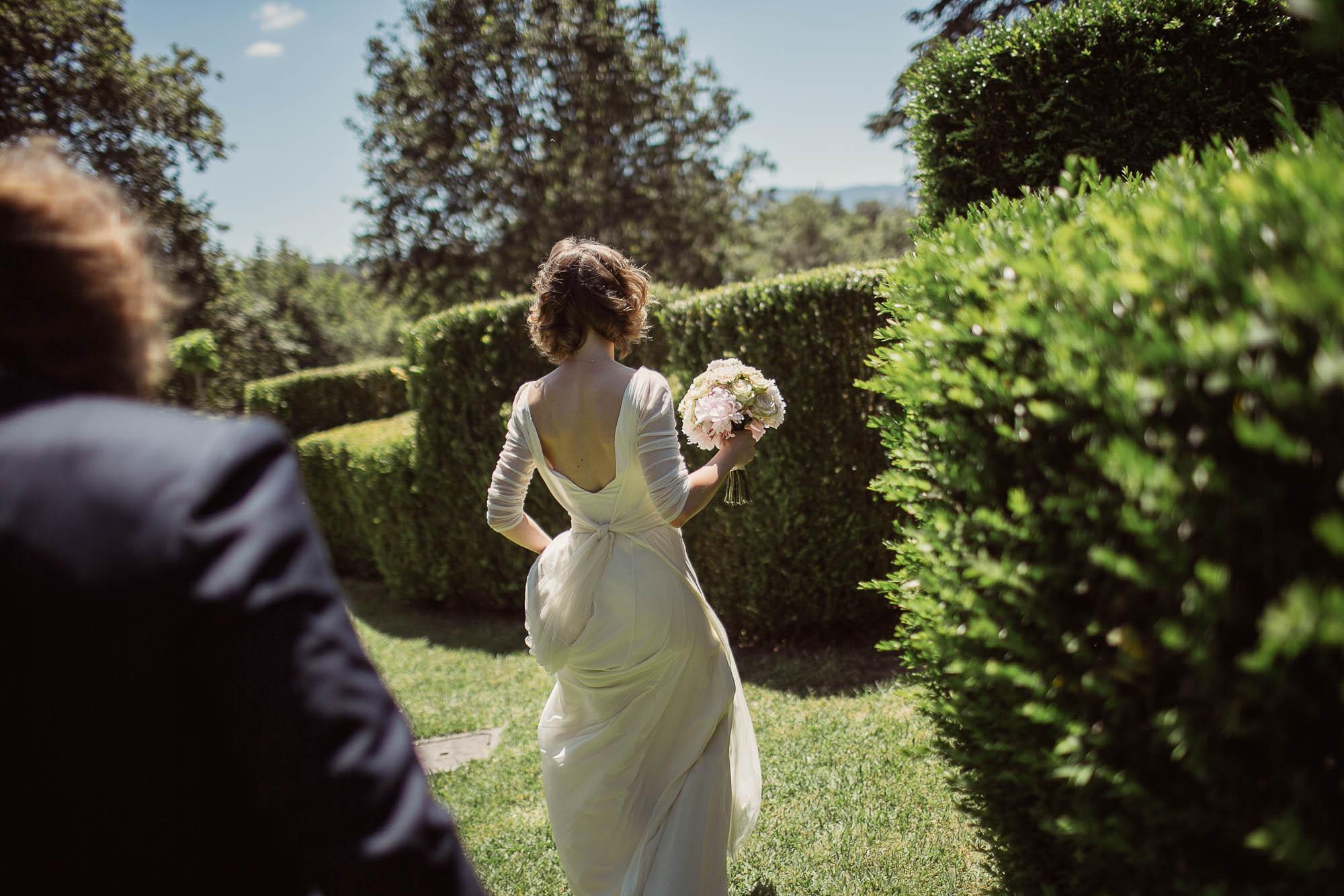 La novia se va corriendo por el jardín de la finca mientras el novio la persigue