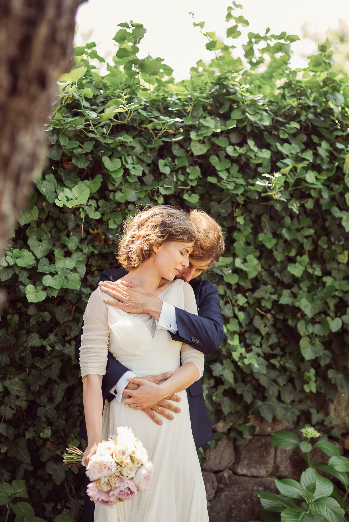 El novio abraza a su mujer cariñosamente mientras ella cierra los ojos y gira la cara hacia él