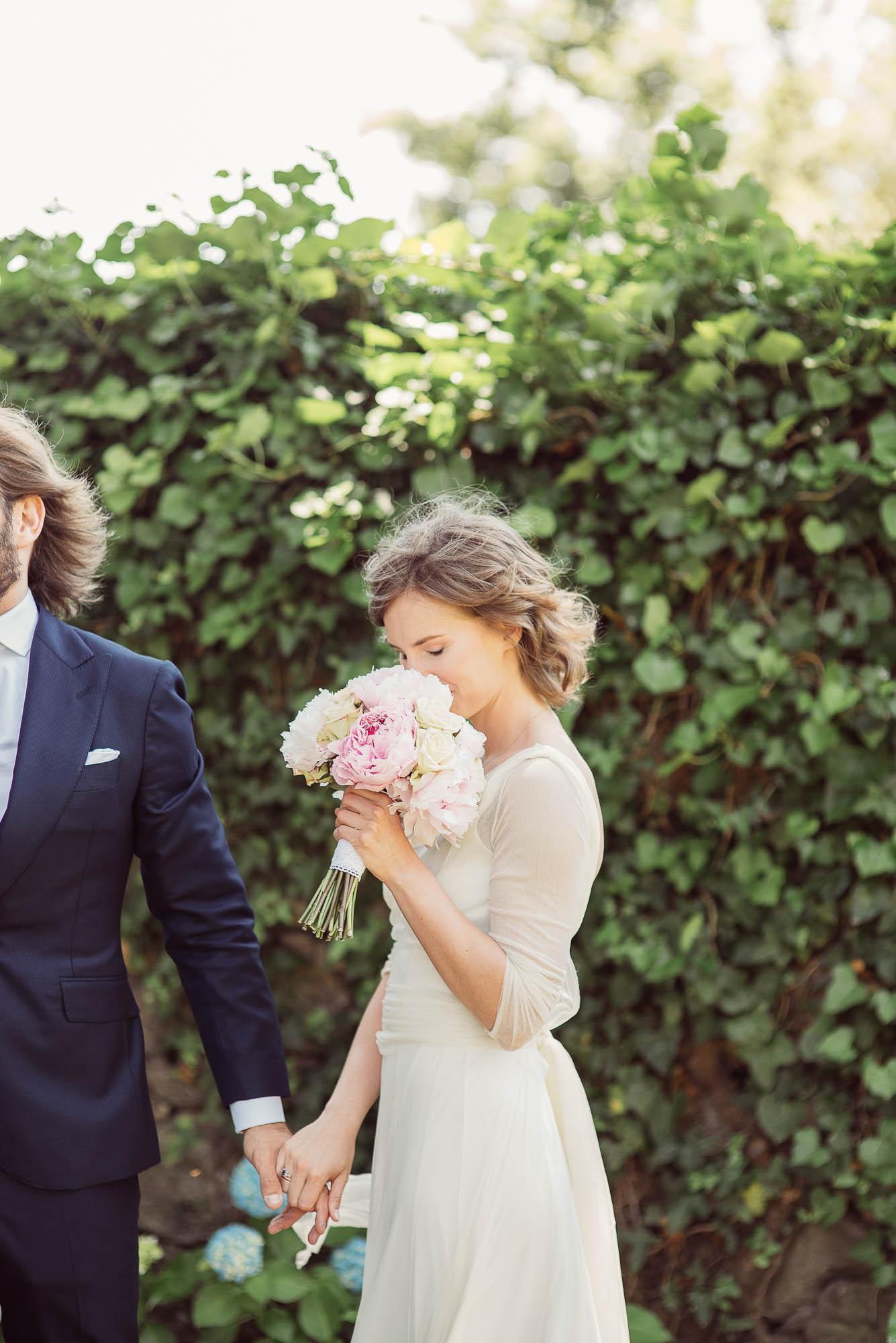 La novia huele el ramo mientras le da la mano a su marido