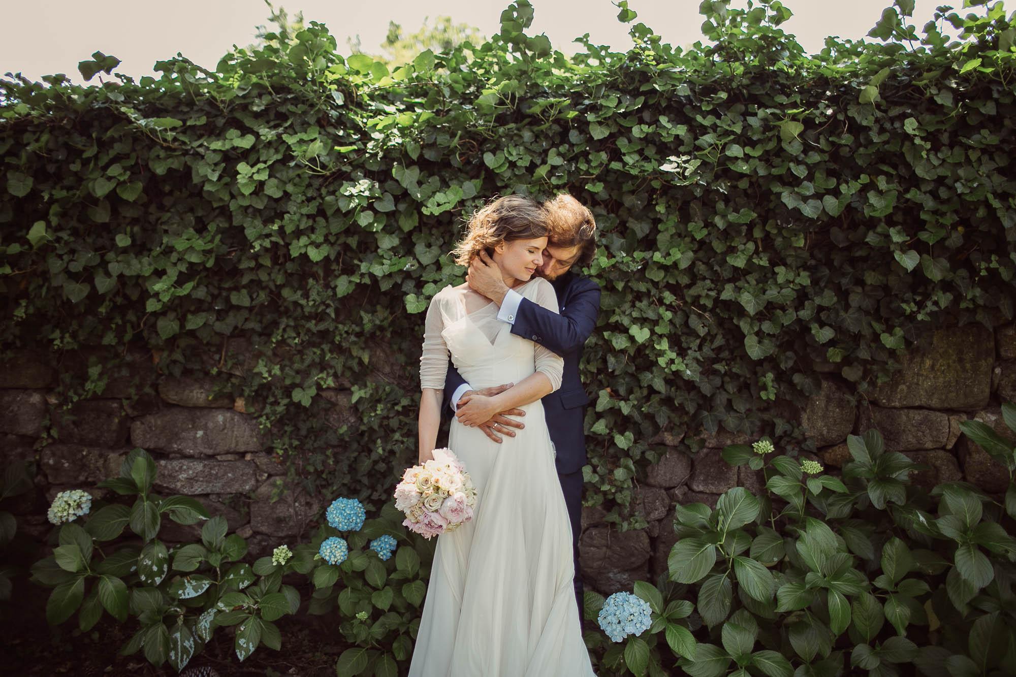 El novio abraza a la novia por detrás mientras se cogen de la mano