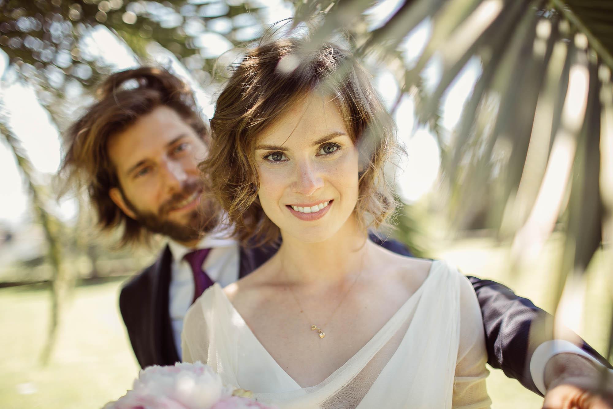 El novio aparece por detrás de la novia bajo la palmera