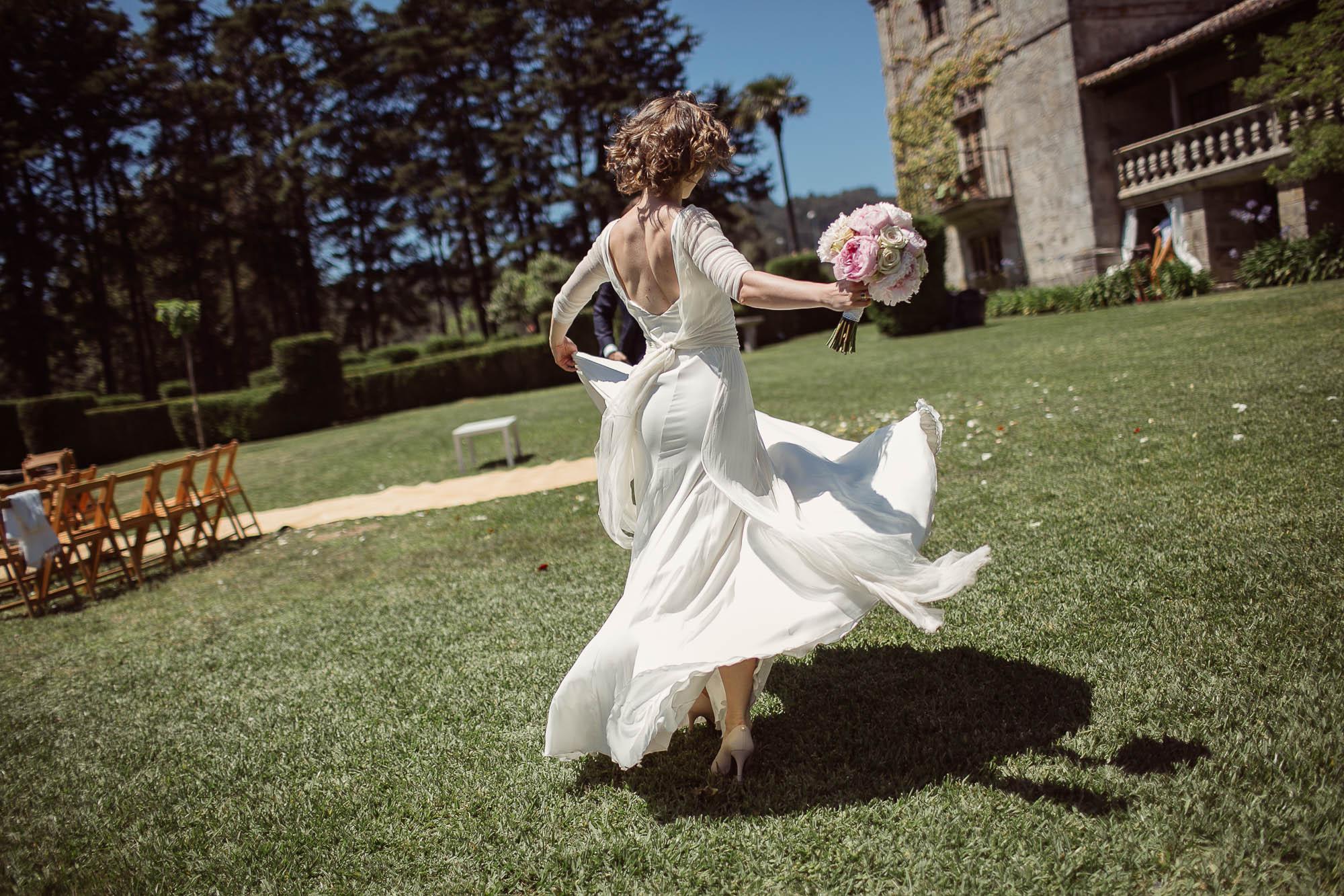 La novia corriendo sujetando el ramo por el jardín de la finca