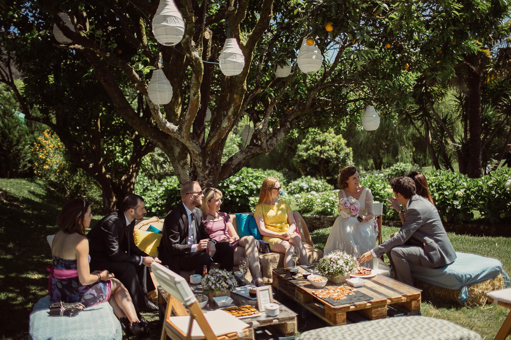 La novia y algunos invitados sentados en unos sillones con unas tapas sobre una mesa de palets bajo un naranjo