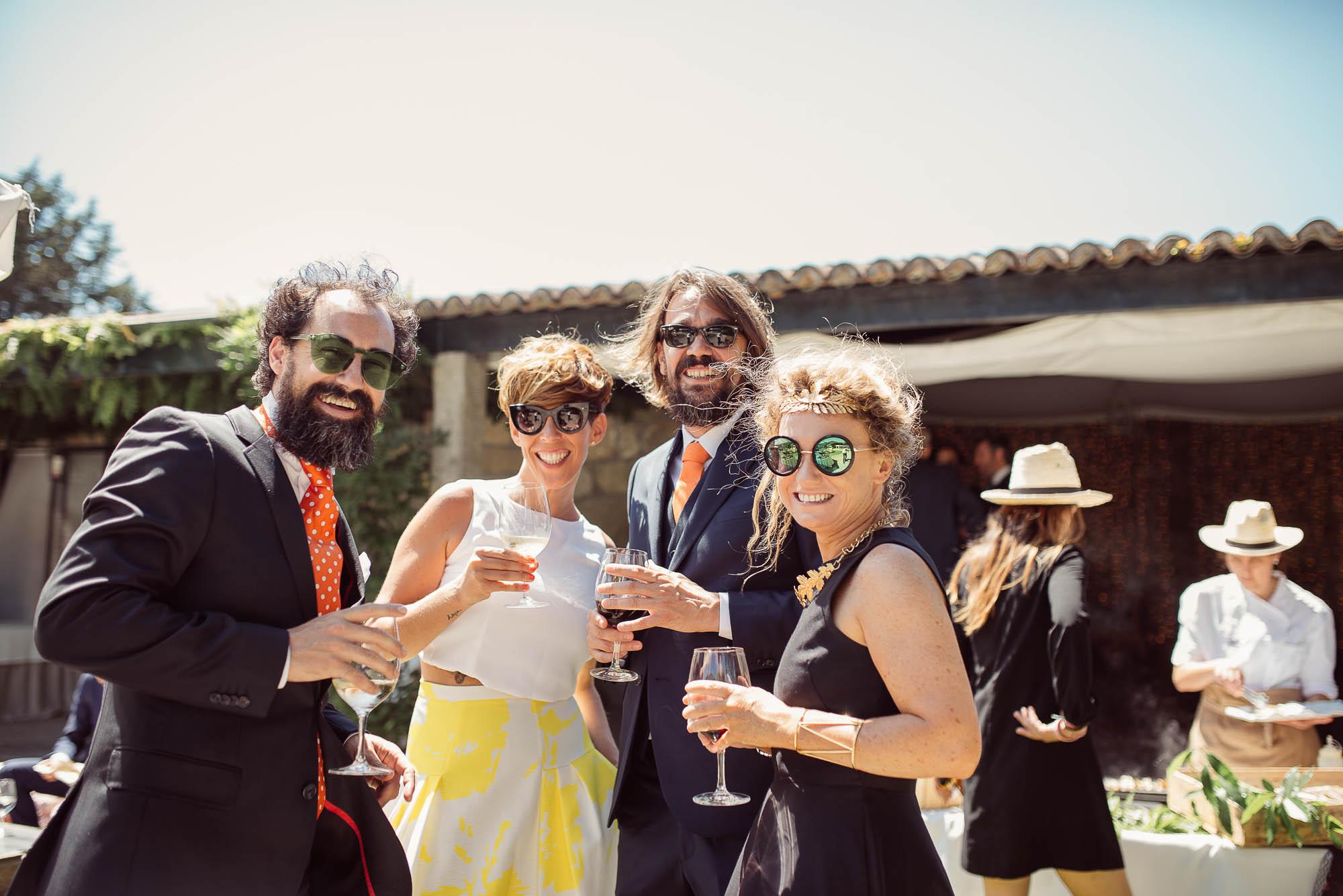 Invitados de la boda sonriendo para una foto mientras sostienen unas copas