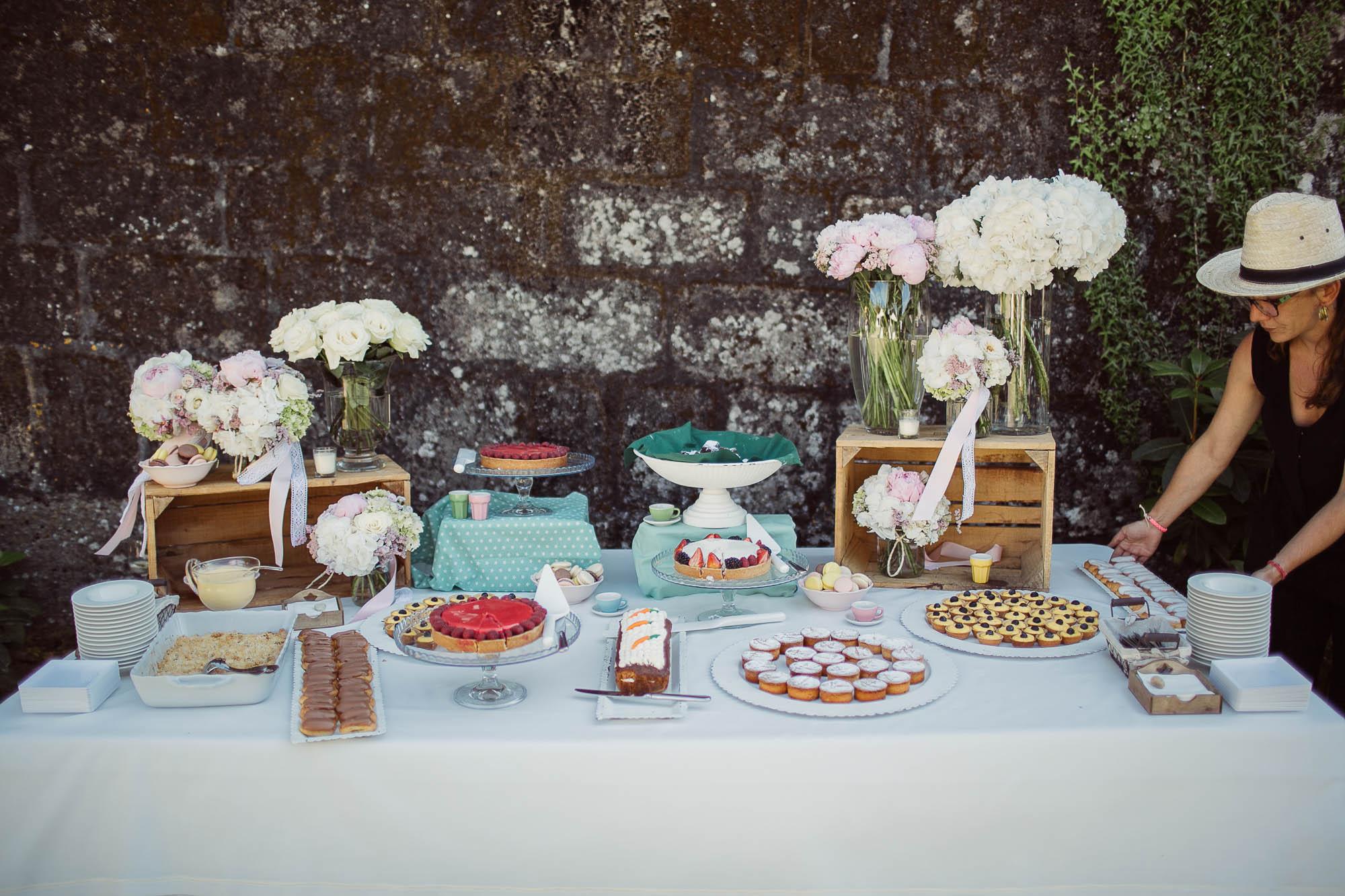 Catering de postres en una mesa con algunos arreglos florales