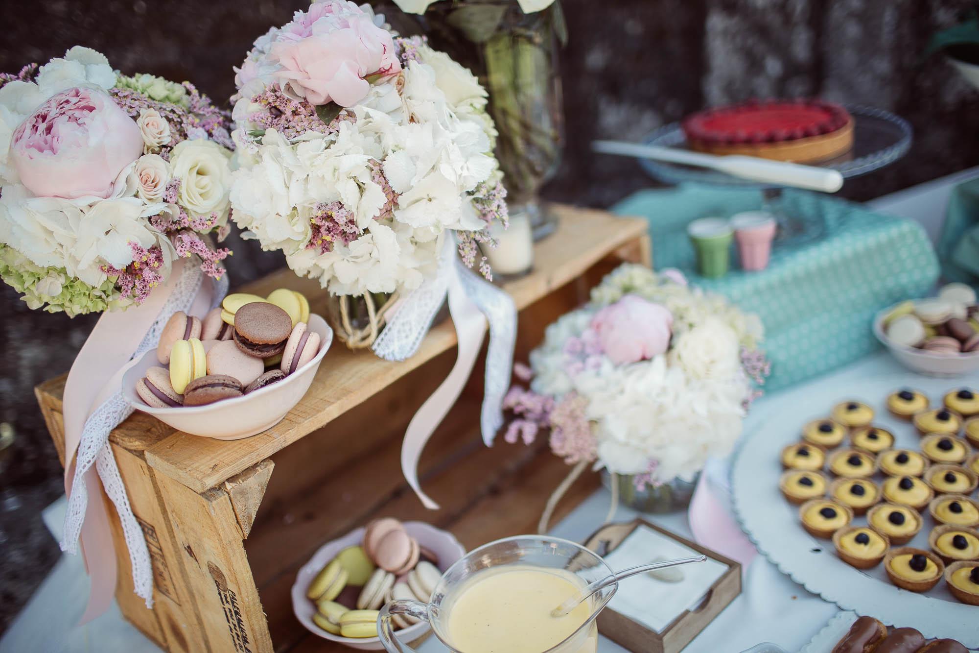 Unos macarons y otros dulces del catering junto con algunos adornos florales