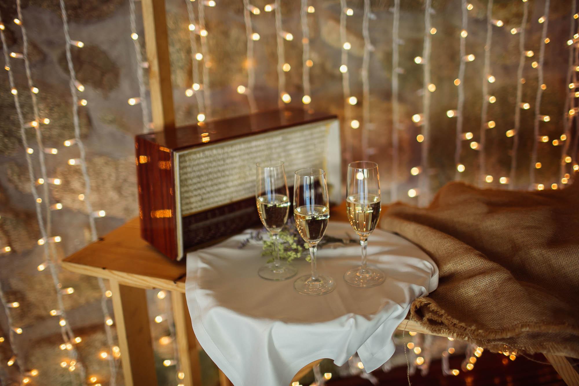 Tres copas sobre una bandeja con un mantel de tela blanca sobre una mesa de madera con un fondo de luces