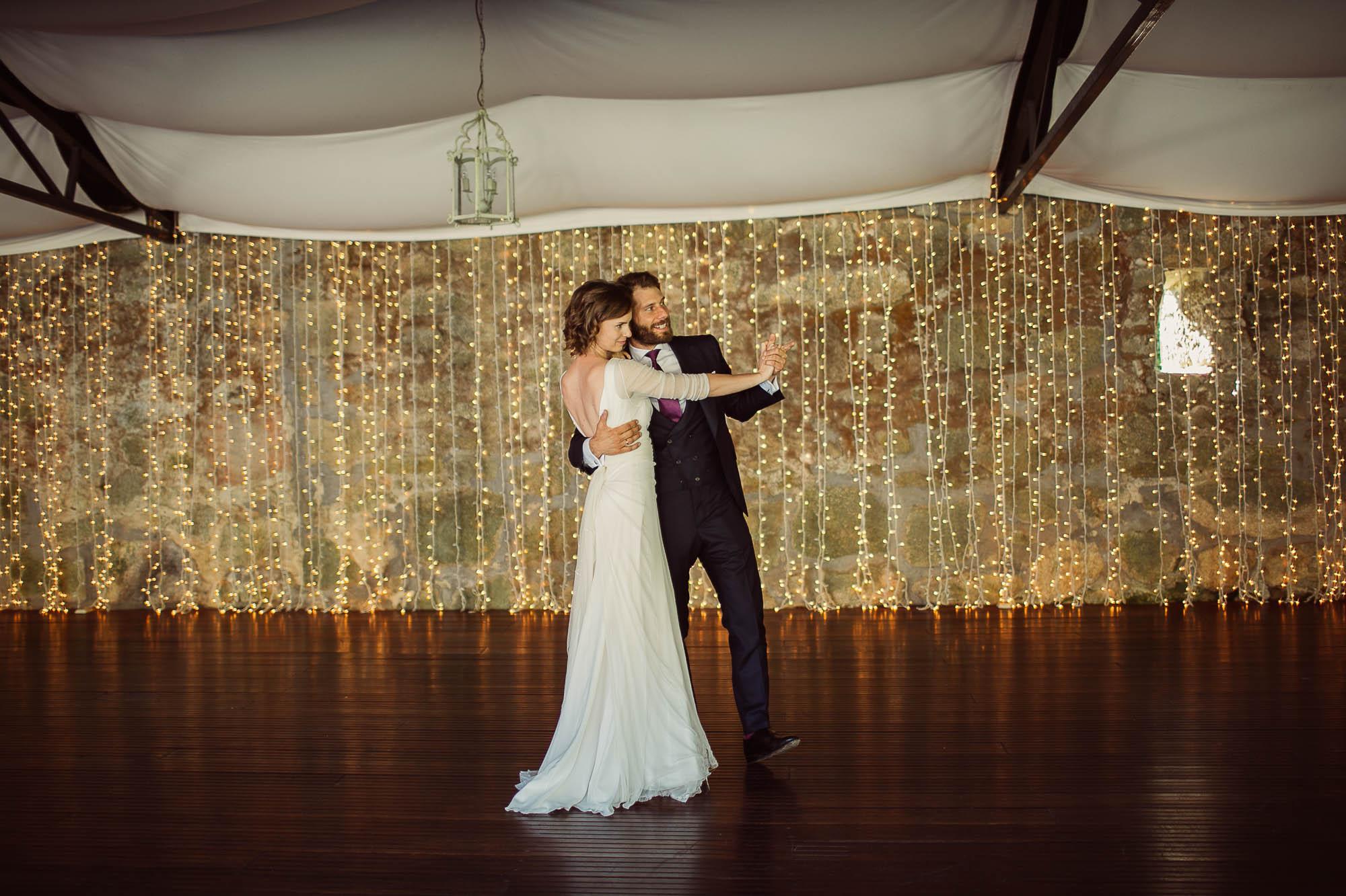 Marido y mujer bailando en un salón con suelo de madera oscura bajo una carpa con un fondo de luces