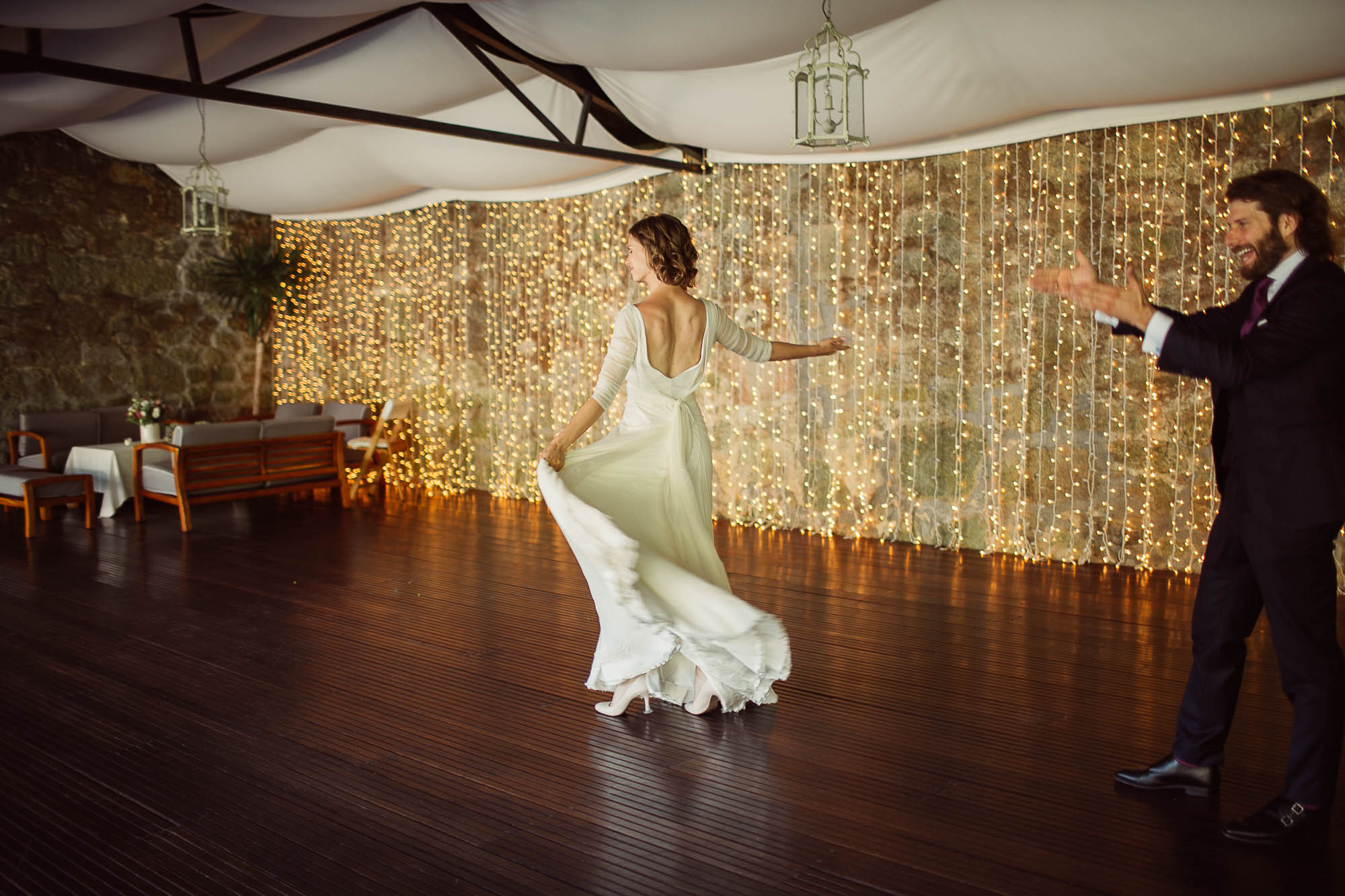 El novio aplaudiendo mientras su mujer da un paso de baile en el centro de la pista